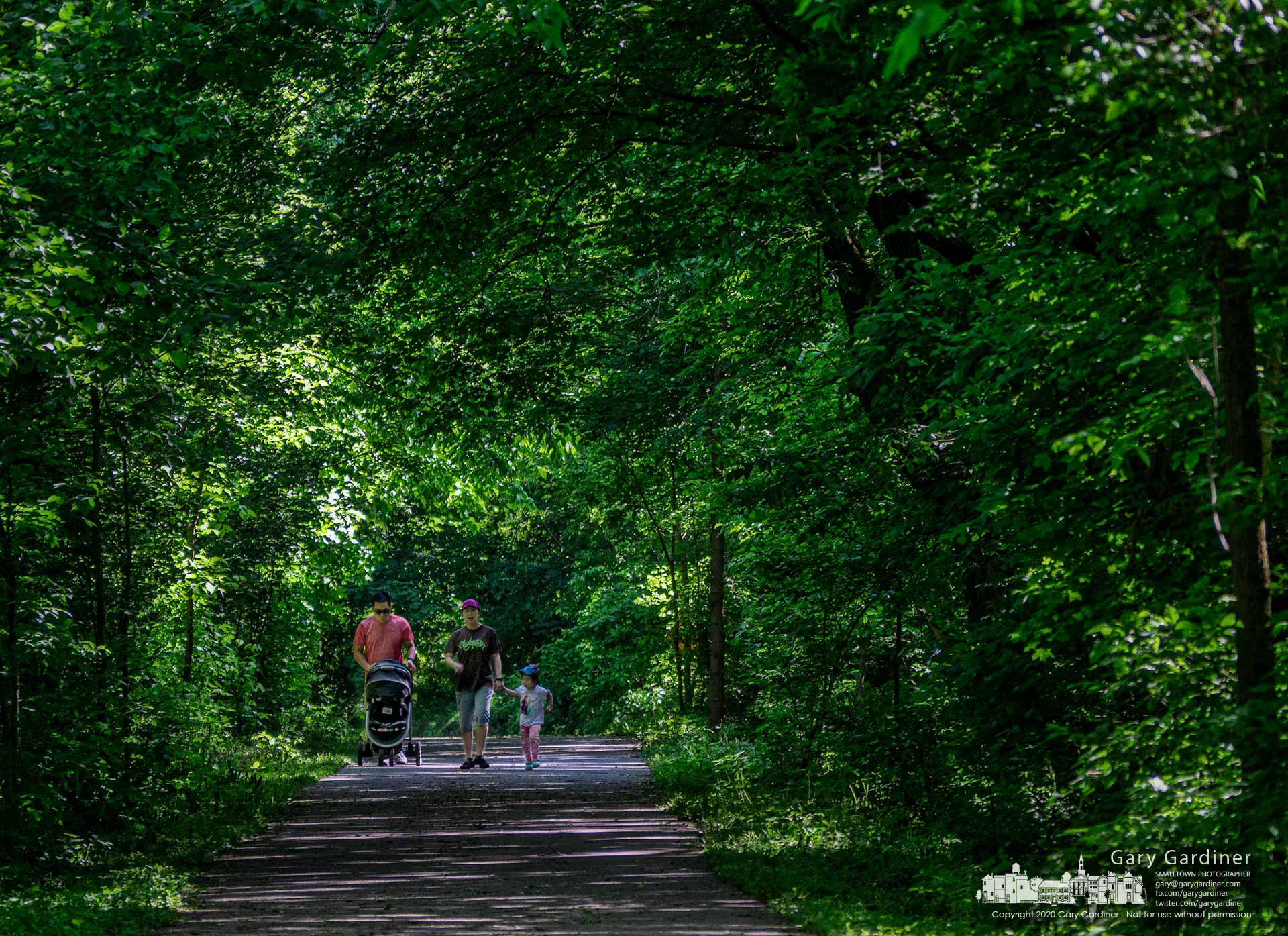 A family walks in the dappled sunlight cast along the tree-shrouded Hoover Scenic Walkway over Big Walnut Creek where it leads into Hoover Reservoir. My Final Photo for May 31, 2020.