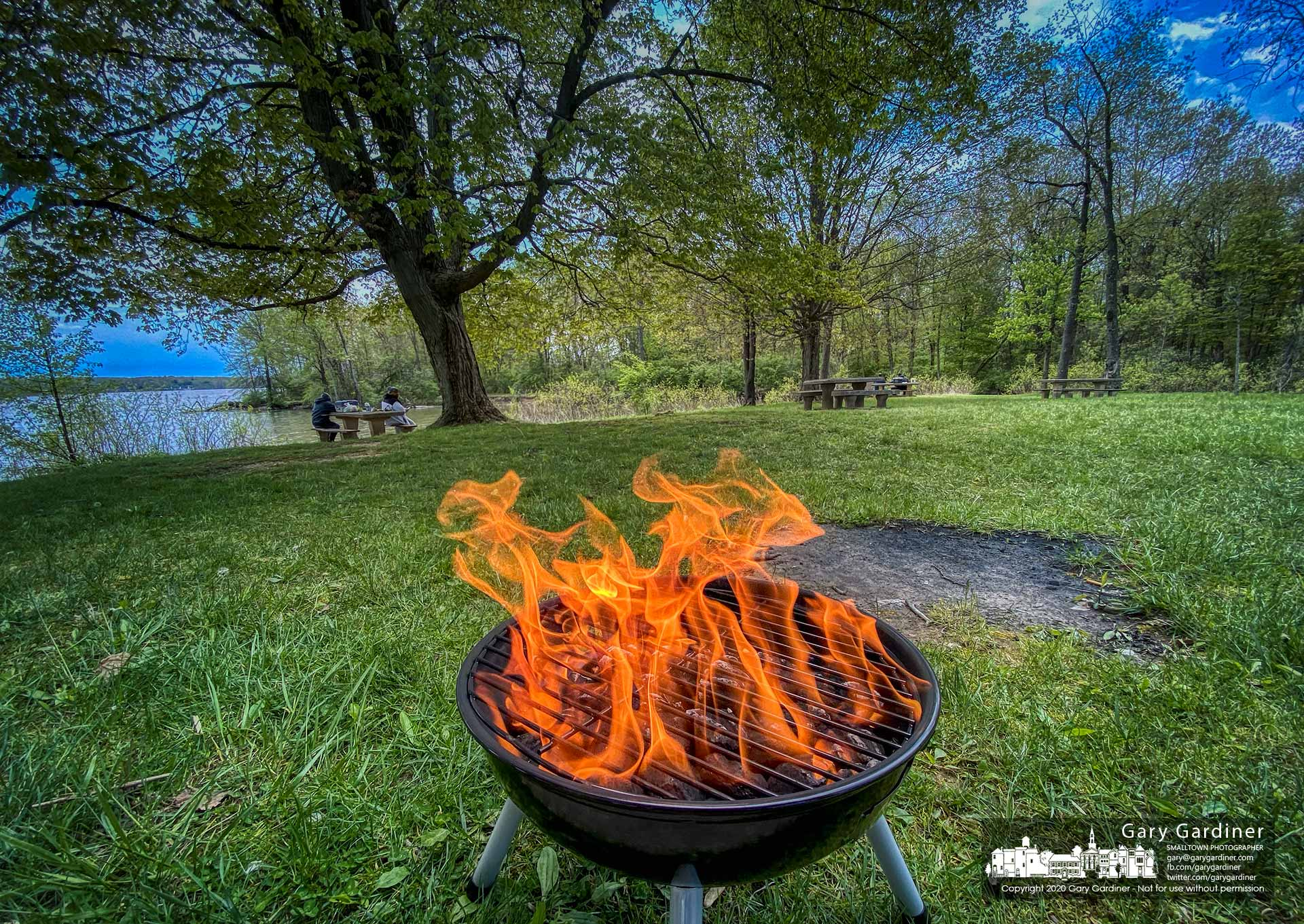 A blazing fire in a charcoal grill signals the beginning of a cookout for a family in the pavilion at Red Bank on the shore of Hoover Reservoir. My Final Photo for May 10, 2020.