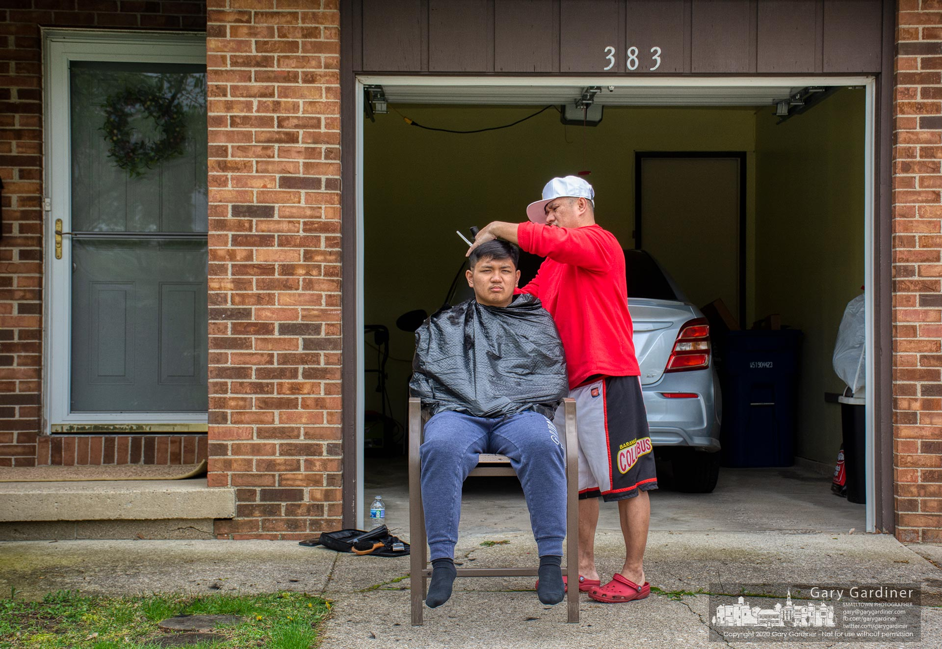 A young man gets his hair cut in the driveway of his duplex apartment on Huber Village Blvd. My Final Photo for May 1, 2020.