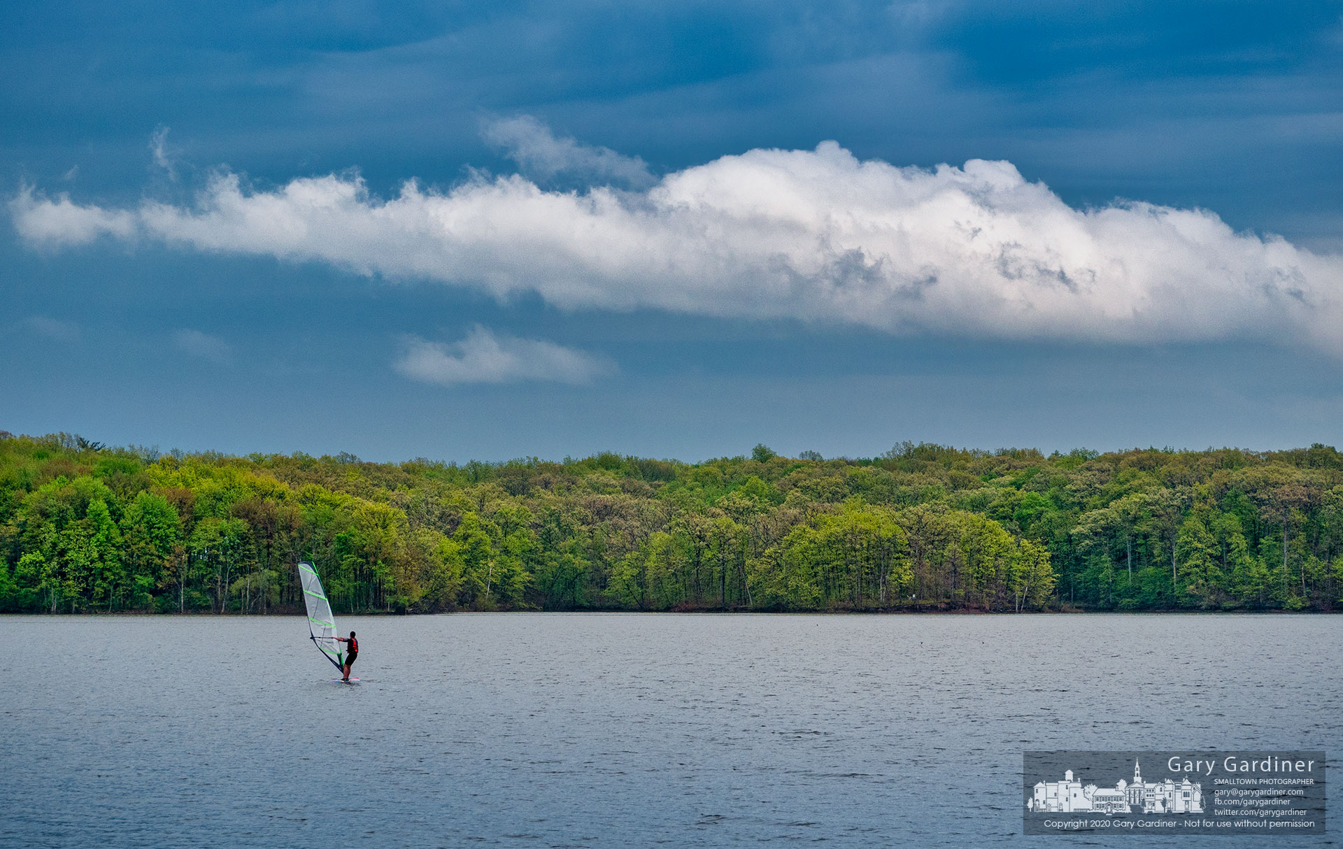 A windsurfer navigates his way across Hoover Reservoir against a panorama of spring colors on the shoreline and stormy weather in the skies. My Final Photo for May 14, 2020.