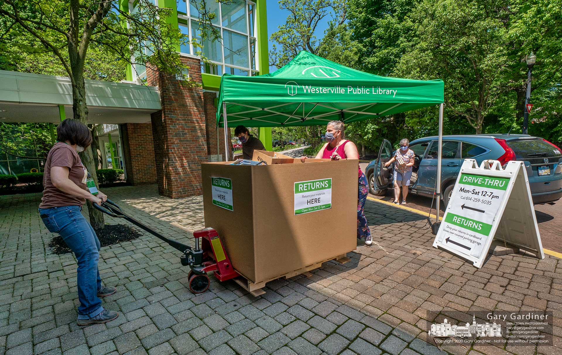 The first box of books filled with books returned to the Westerville Public Library by patrons is wheeled into the building as more patrons use the drive-thru process to return books kept in their homes during the coronavirus pandemic closing. My Final Photo for May 26, 2020.
