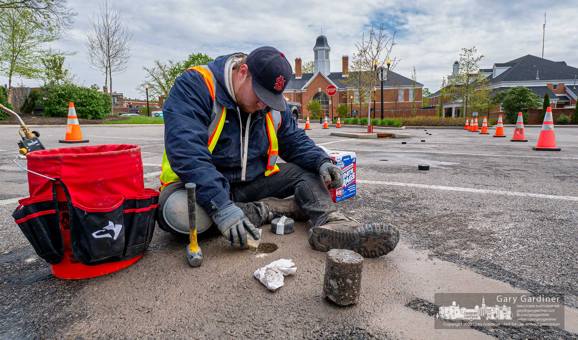 A work crew installs sensors in the parking lot behind city hall as part of the program to monitor and collect data on city-owned parking lots and includes the use of a mobile app for shoppers. My Final Photo for May 6, 2020.
