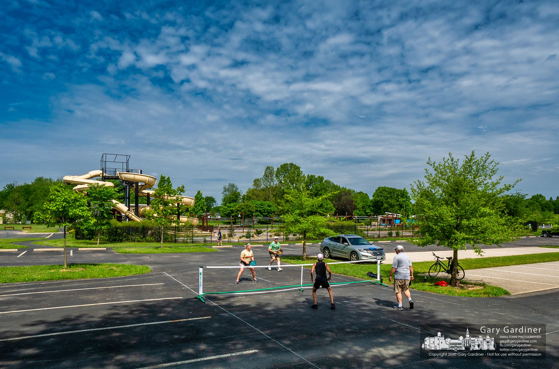 A foursome uses a section of the Highlands Pool parking lot as their private pickleball court taking advantage of the pool being closed because of the coronavirus pandemic. My Final Photo for May 27, 2020.