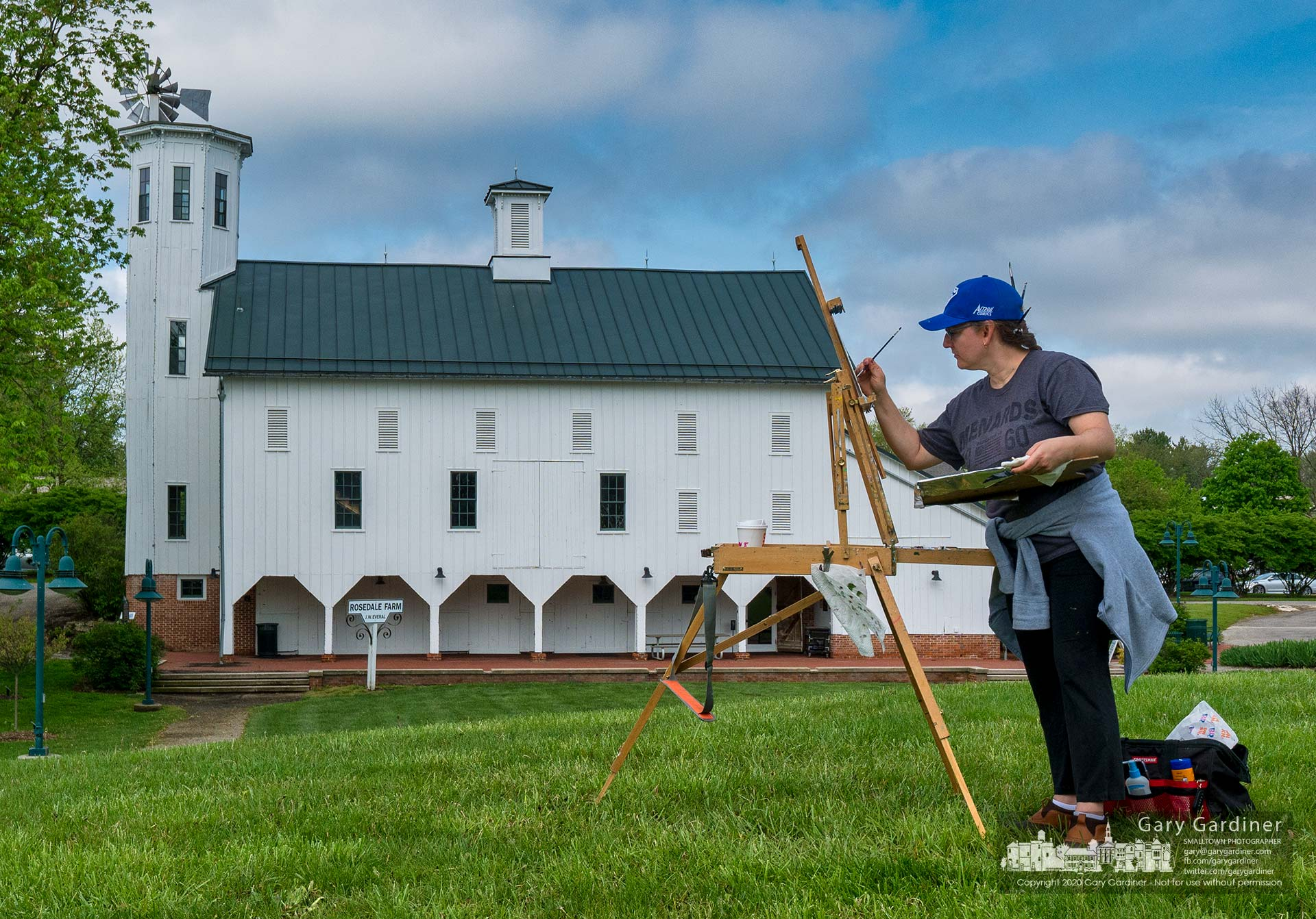 A Plein air artist stands atop the small hill adjacent to the Everal Barn at Heritage Park as she and a group of other artists spent the warm spring morning creating art of the park. My Final Photo for May 16, 2020.
