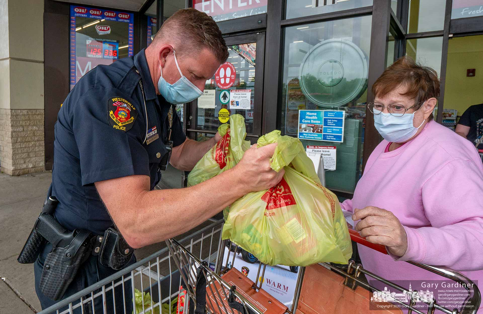 A Westerville police officer helps a woman unload groceries from her cart as a donation for W.A.R.M. during the department's Fill-A-Cruiser food drive. My Final Photo for May 28, 2020.