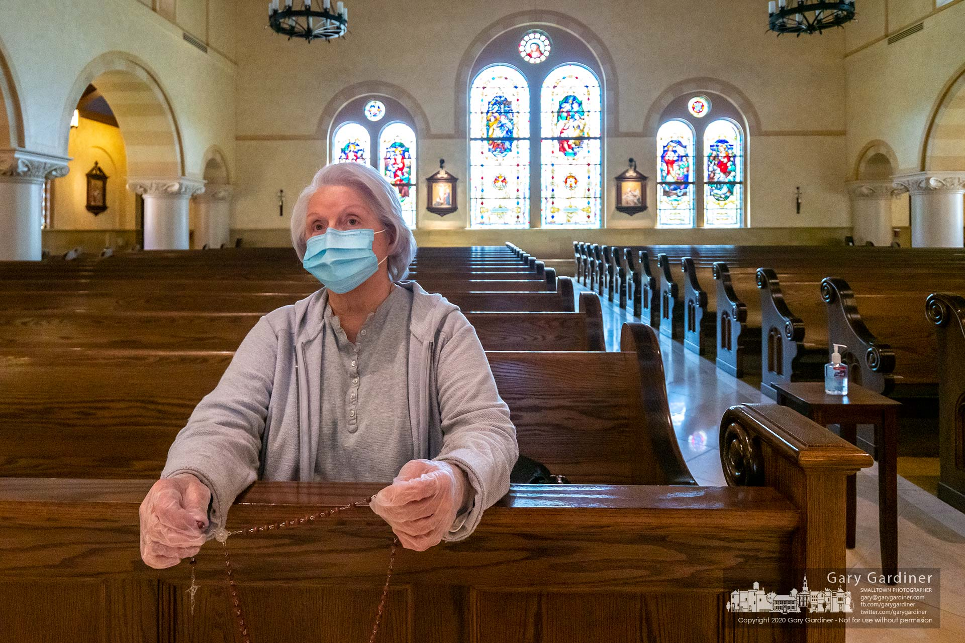 A parishioner prays while wearing a face mask and rubber gloves with hand sanitizer on a table in the aisle after St. Paul the Apostle Catholic Church opened its doors after closing them two months ago due to the coronavirus pandemic. My Final Photo for May 13, 2020.