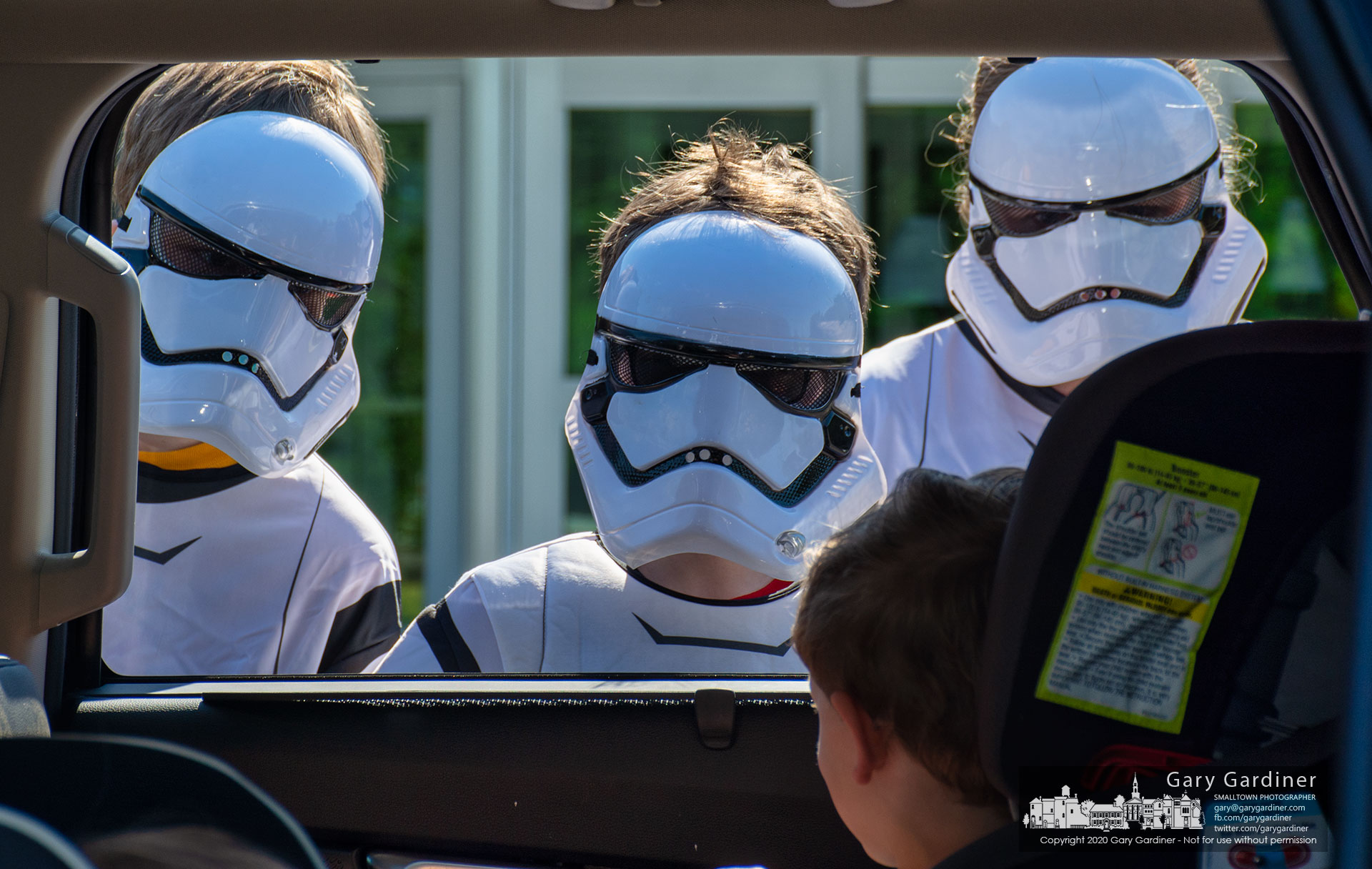 A trio of Stormtroopers asks a youngster in a car seat if he has any droids in the car as he passes a checkpoint in front of the Westerville Community Center during a food drive e for W.A.R.M. My Final Photo for May 30, 2020.