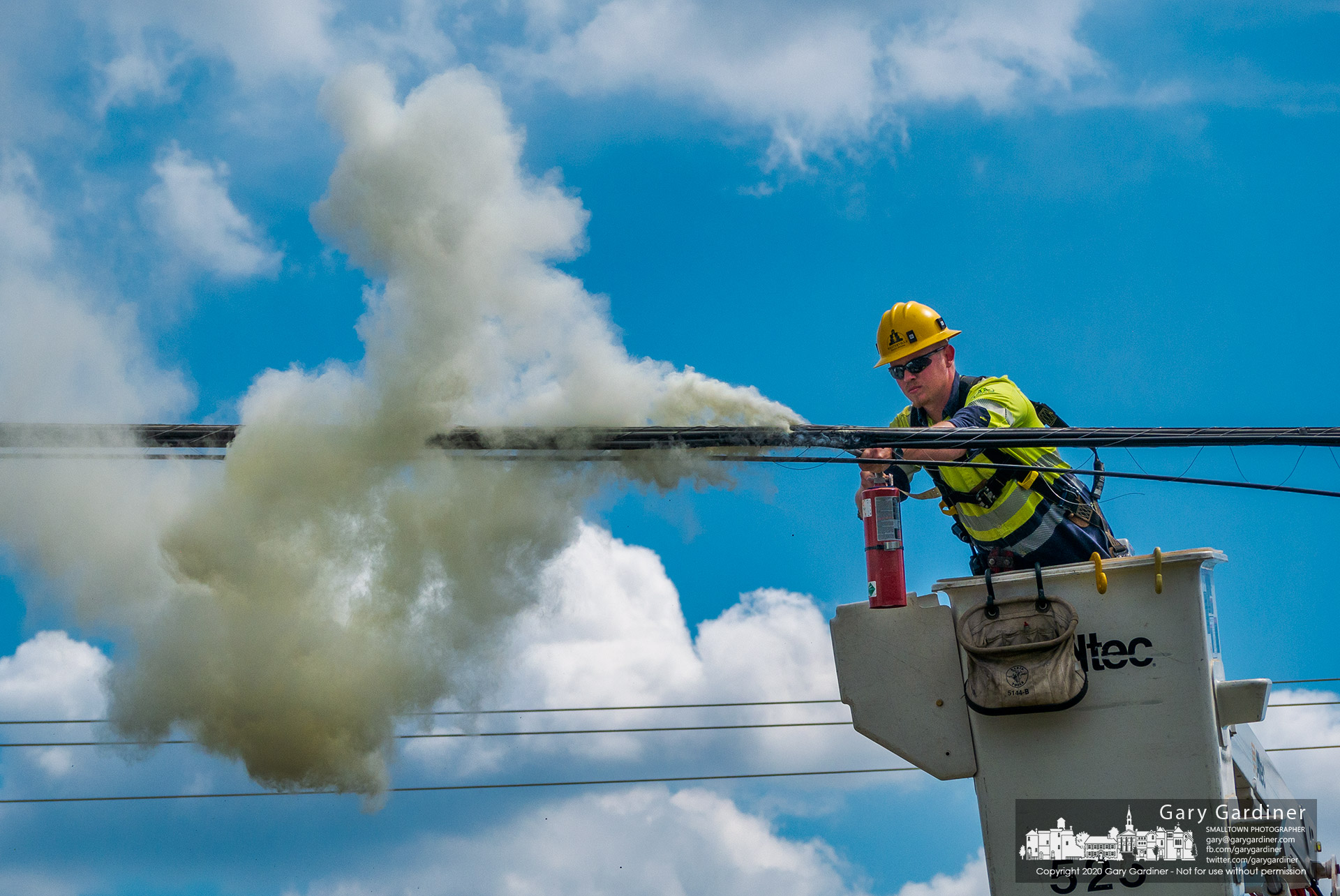 A city electric worker sprays a fire extinguisher on a section of plastic wrap around utility cabling that caught fire in the afternoon from an unknown source near West Main and Cleveland Ave. My Final Photo for June 19, 2020.