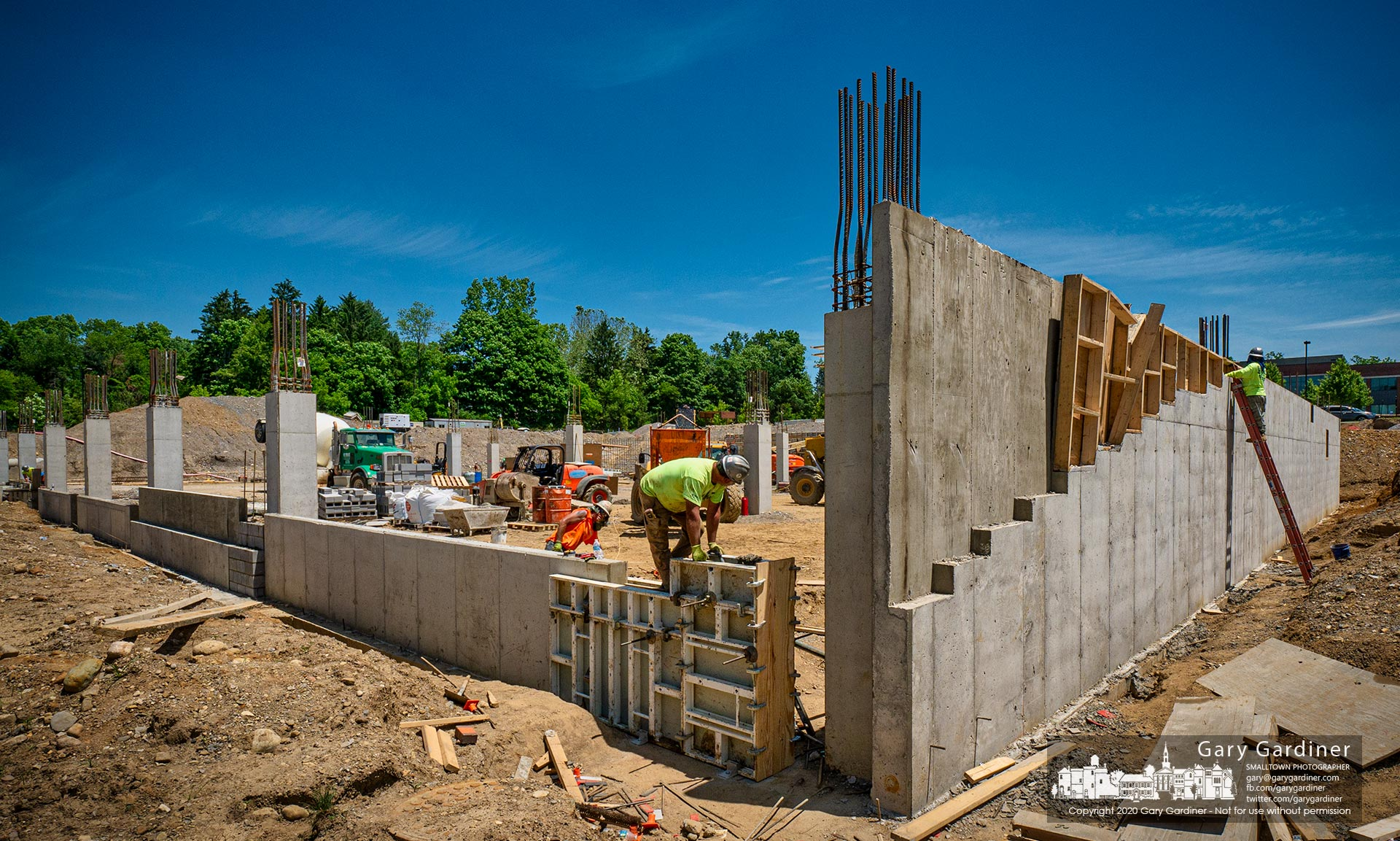 Workers erect formed concrete walls of the first-floor parking garage for the new COPC care center being built adjacent to its two existing building off Africa Road. My Final Photo for June 9, 2020.