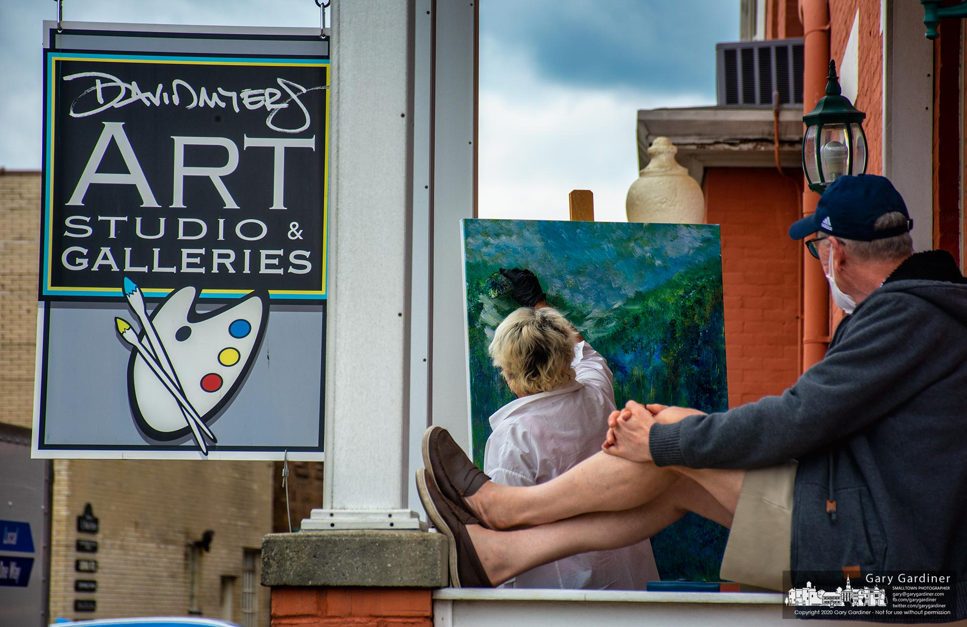 Westerville artist David Myers rests on the railing of the portico of his gallery as one of his students takes advantage of the weather to complete her work outdoors. My Final Photo for June 15, 2020