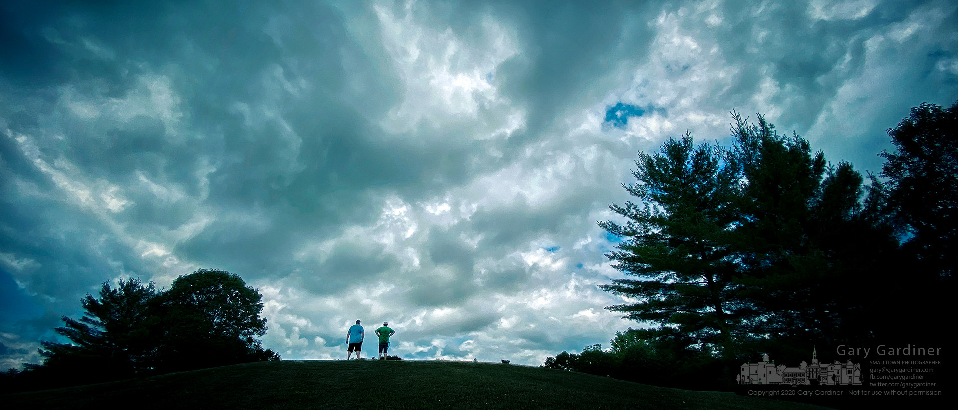 Two fathers stand atop a small hill at the edge of the Highlands wetlands to watch over their children playing in the soccer fields under story skies. My Final Photo for June 22, 2020.