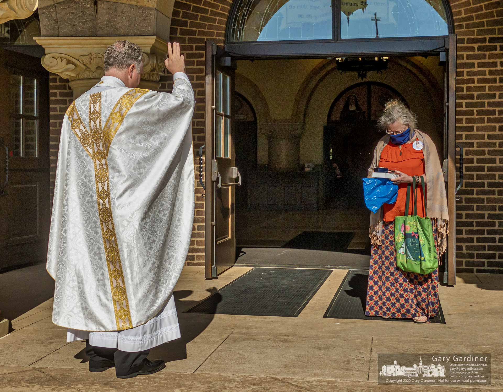 Fr. Jonathan Wilson stands at the prescribed social distance and blesses a woman's religious articles after Sunday Mass at St. Paul the Apostle Catholic Church. My Final Photo for June 7, 2020.