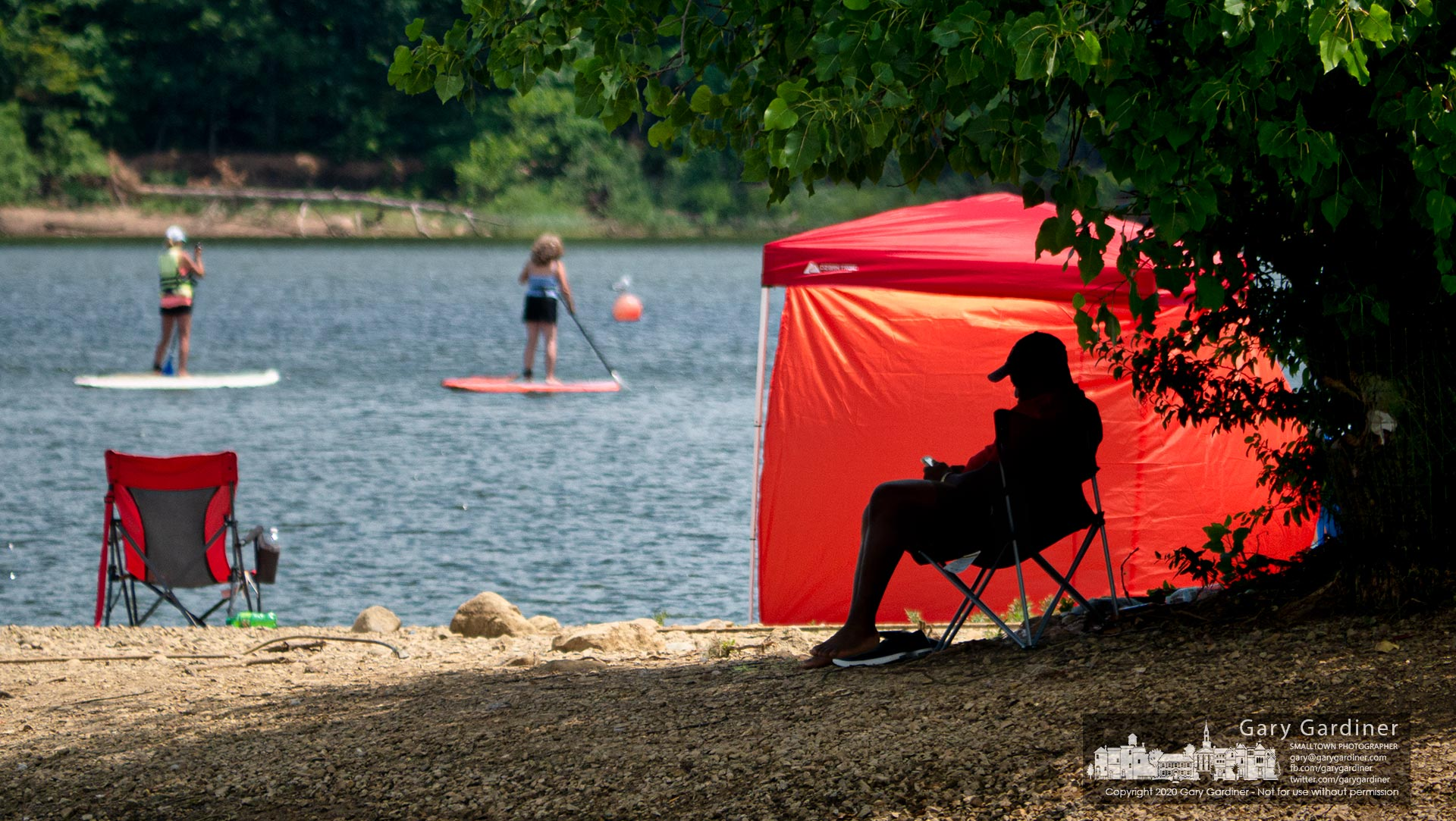 A man sits in the shade of a tree along the shoreline of Hoover Reservoir where a pair of paddleboarders navigate their way across the still waters of the lake. My Final Photo for July 25, 2020.