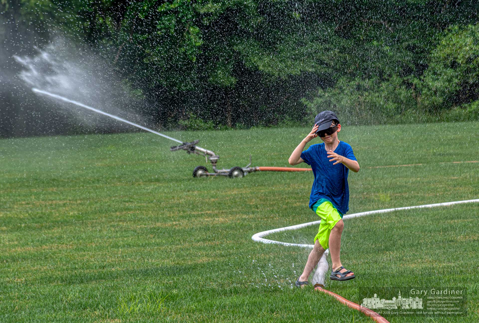 A young boy splashes through spray from a leaky hose fitting and the spray from a sprinkler on one of the practice fields at Otterbein University. My Final Photo for July 7, 2020.