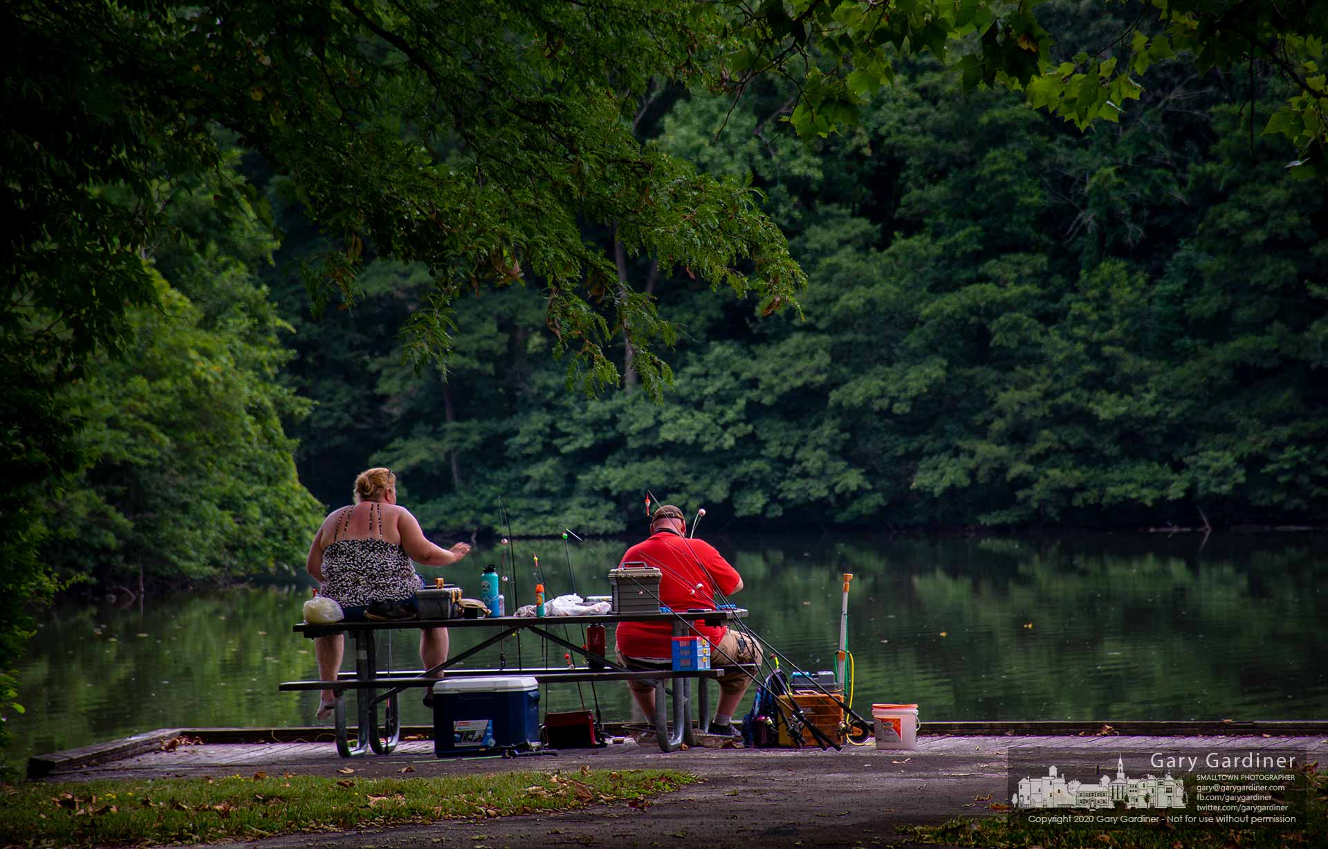 Two people sit at a picnic table with a variety of rods and reels for themselves and their children as they fish at the pond in Sharon Woods Metro Park. My Final Photo for July 30, 2020.