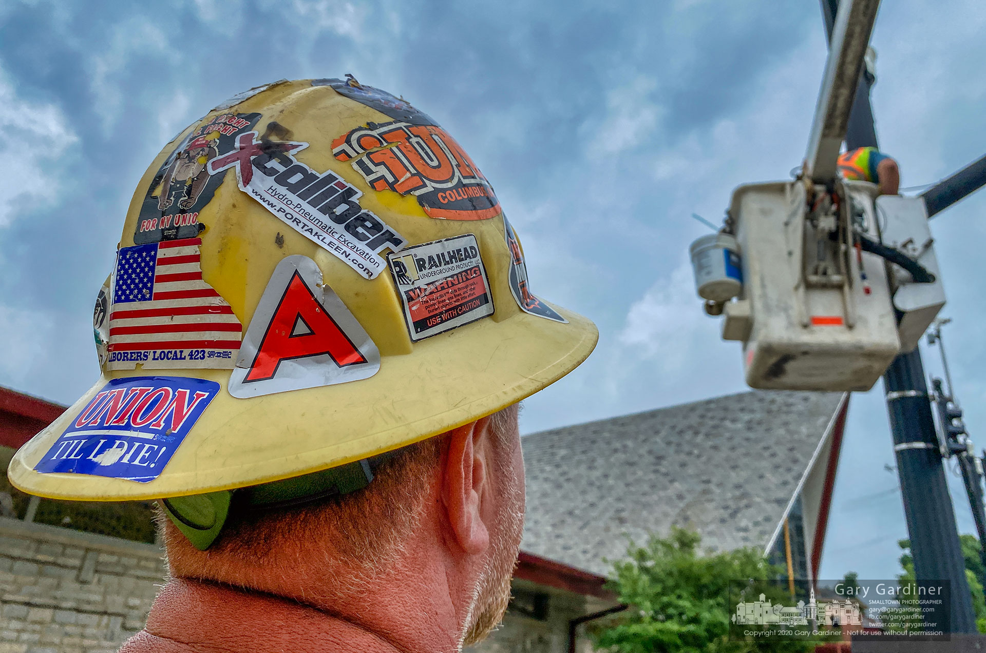 A construction worker's hardhat bears stickers emblematic of his job as part of the electric crew repairing streetlights and traffic signals in Uptown as part for the Uptown Improvement Project. My Final Photo for July 23, 2020.