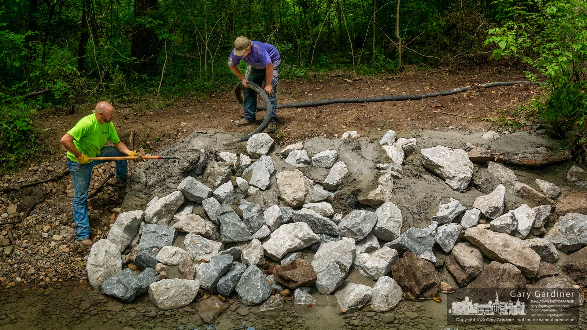 Contractors pump concrete into the void between rocks placed into the edge of Alkire Run to mediate erosion near the bridge on the path that leads to the fields adjacent to the Community Center. My Final Photo for Aug. 11, 2020.