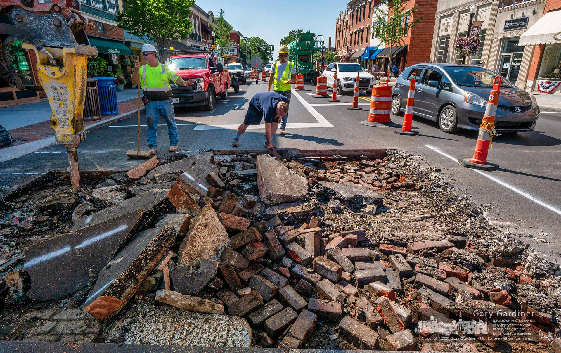 A man reaches to retrieve a brick ripped up from below State Street at Main Street where the next phase of the Uptown Improvement Project includes new brick crosswalks. My Final Photo for Aug. 7, 2020.
