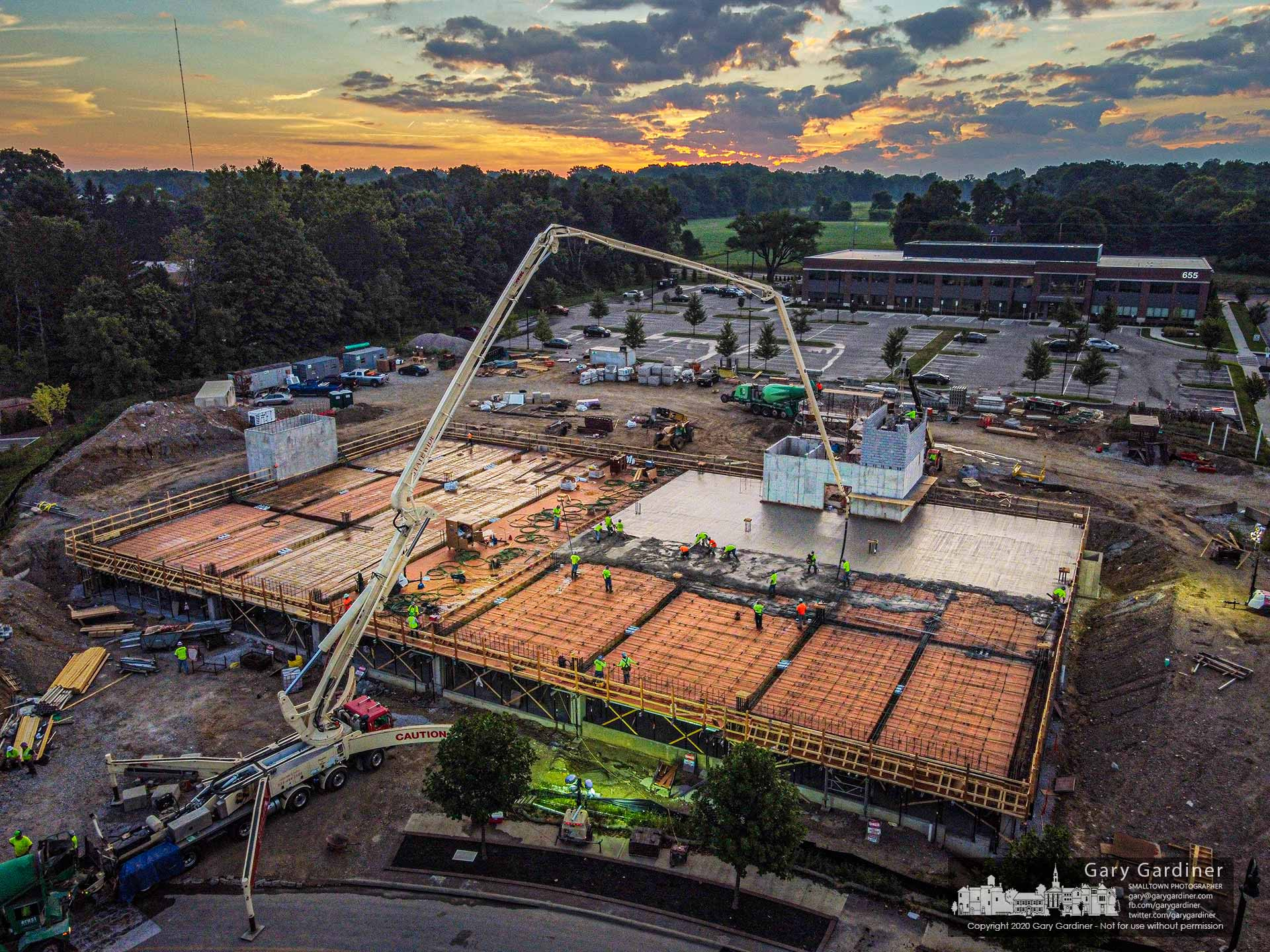 The morning begins to show as concrete is pumped onto the second-floor garage section of the COPC offices being built behind the company's other two buildings on Africa Road.