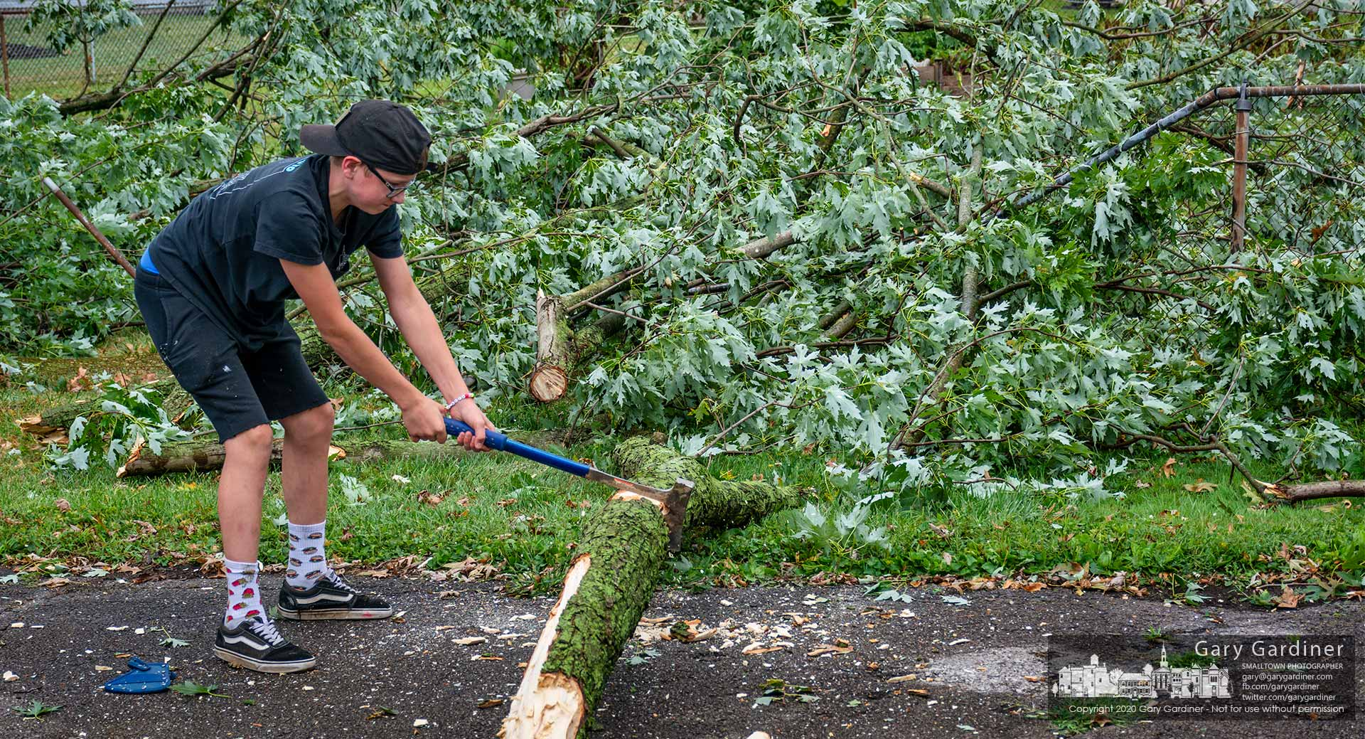 A teenager uses his family's ax to chop up sections of the silver maple tree that fell in their back yard and neighbors smashing a chain-link fence with little damage to other structures. My Final Photo for August 28, 2020.