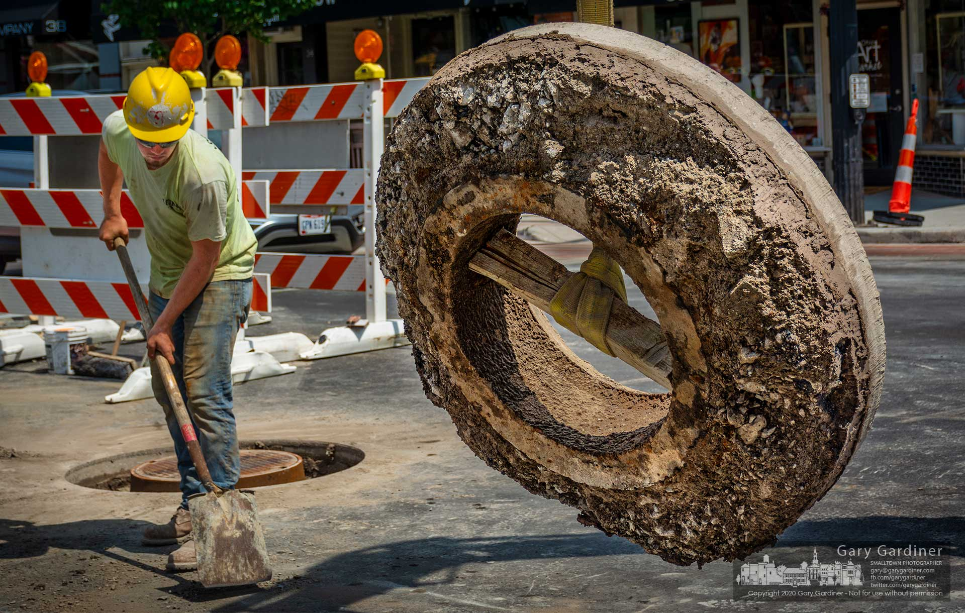 A worker clears debris around the concrete, asphalt, and steel donut removed from a manhole cover at State and Main where an upgraded cover will be installed after State Street was rebuilt. My Final Photo for Aug. 25, 2020.