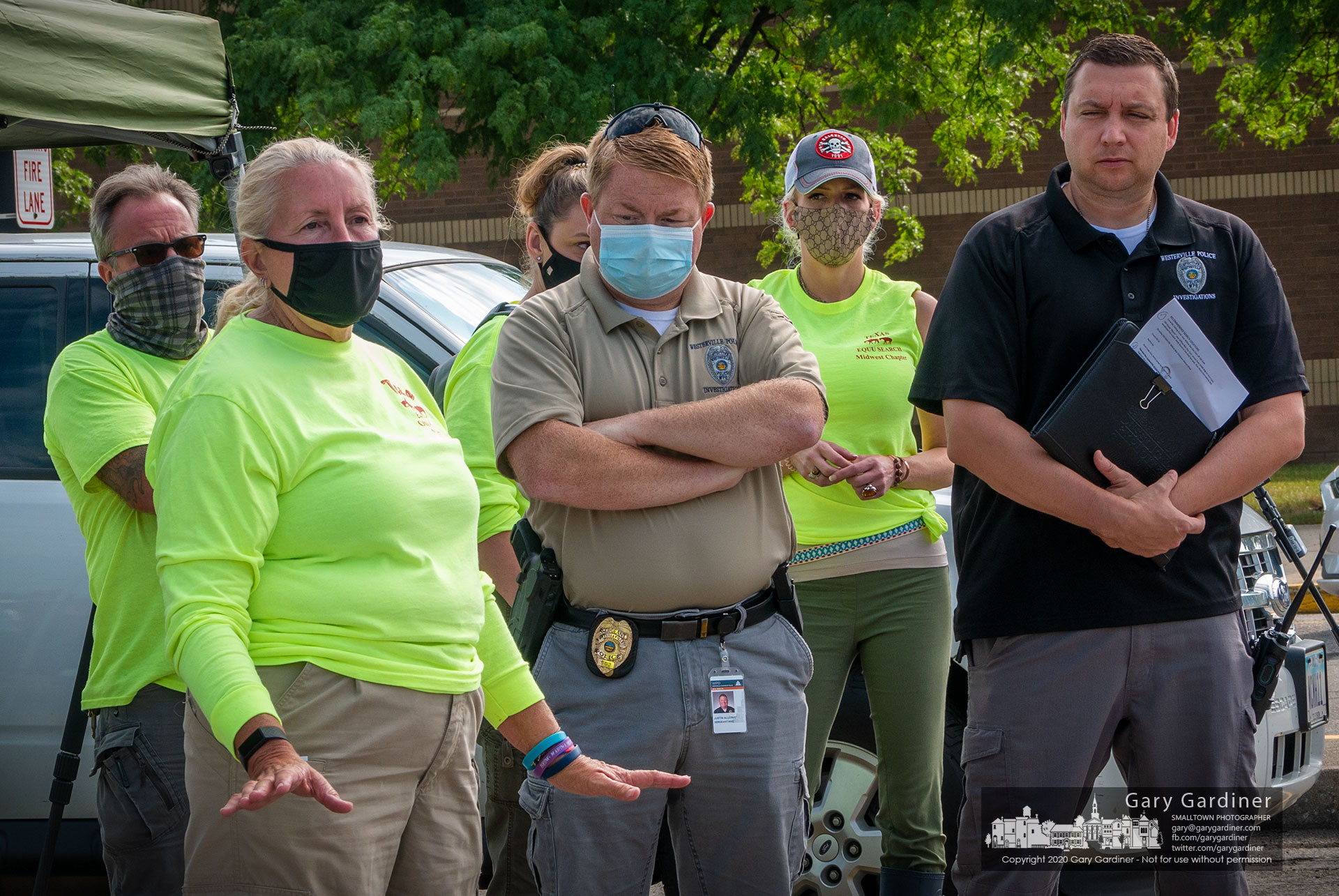 Westerville Police Officer Justin Alloway, center, listens as instructions are given to people who gathered at Westerville North High School Sunday morning to search for Emily Noble who's been missing for about three months. My Final Photo for Aug. 16, 2020.