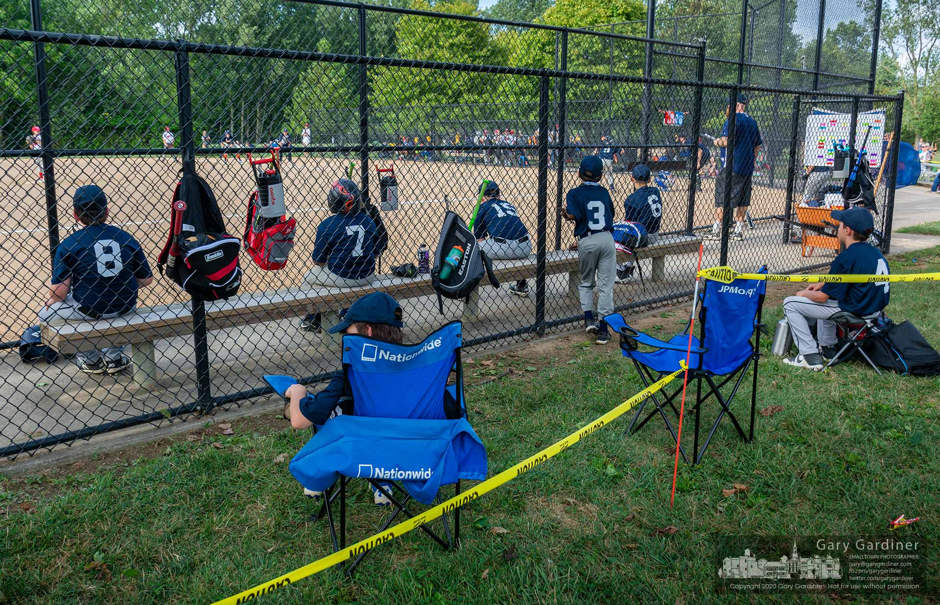 A youth baseball team sits in an improvised socially distanced bench at one of the fields at Huber Village Park. My Final Photo for Aug. 27, 2020.