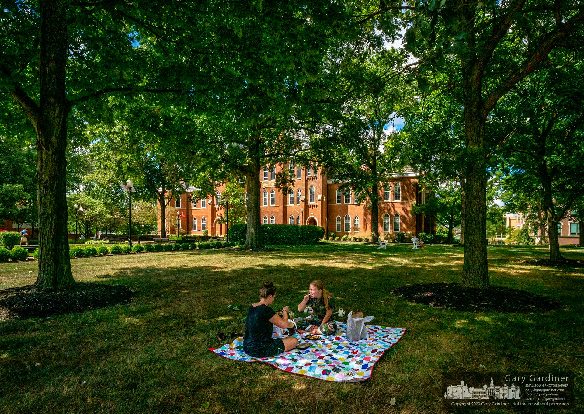 Using a family quilt, two women eat their lunch of the lawn at Towers Hall at Otterbein University. My Final Photo for Aug. 19, 2020.