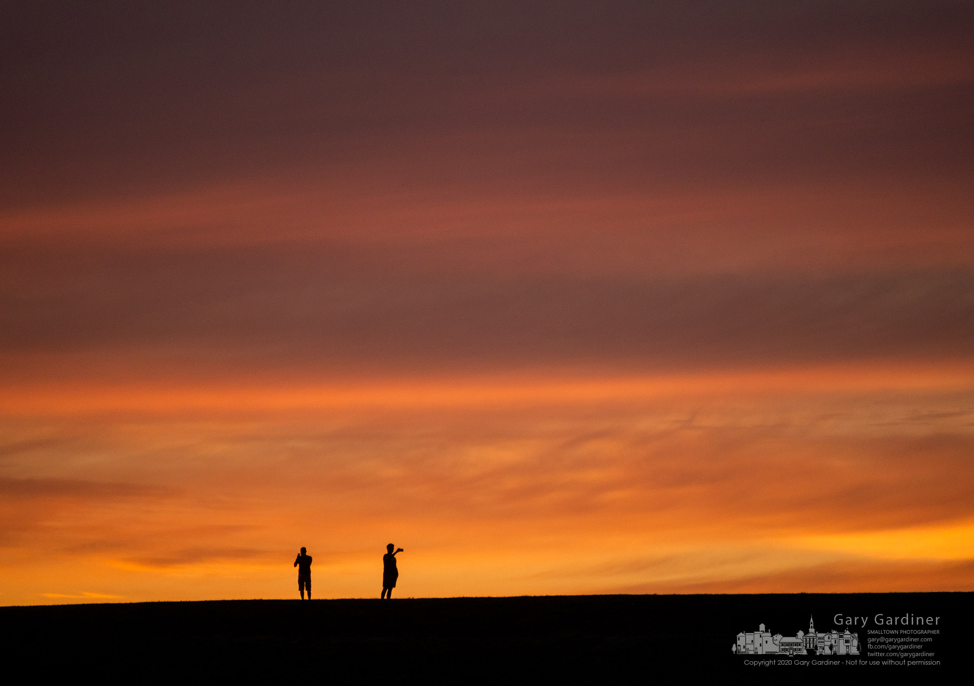 Two men pause during their walk atop the Alum Creek Dam to photograph the sunset across the lake using their phones. My Final Photo for Aug. 30, 2020.