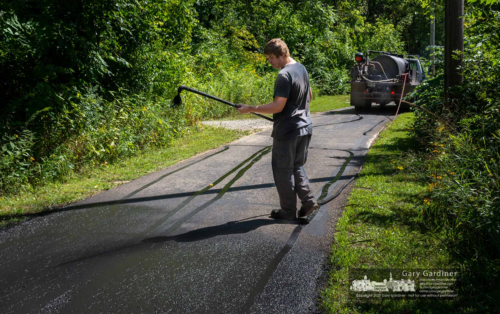 A worker sprays blacktop seal on the section of the bike path between Alum Creek and Otterbein Lake as he moves toward finishing the day on the path near I-270. My Final Photo for Sept. 4, 2020.