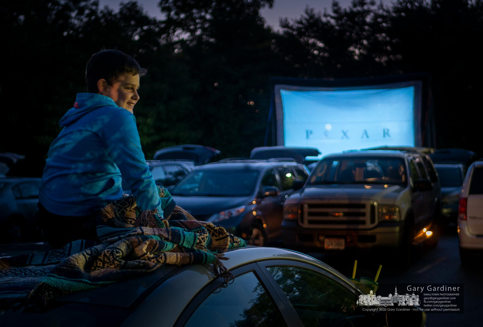 """A boy sitting on the roof of his family car smiles at the opening credits for """"Toy Story"""" on an outdoor screen at the Westerville Fair Food Fest on its first day. My Final Photo for Sept. 18, 2020."""