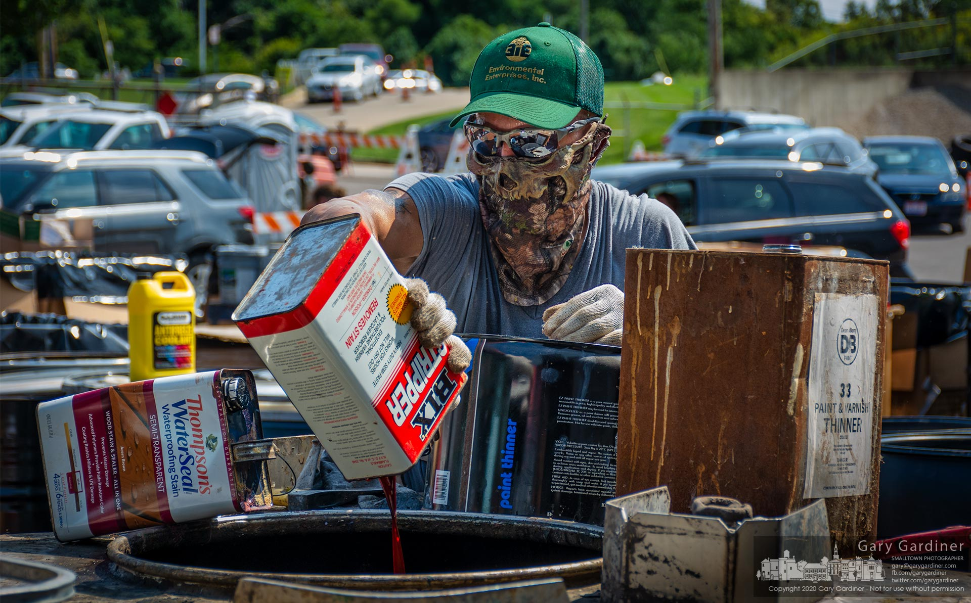 A worker empties discarded petroleum products into a container during a hazardous waste disposal event where everything from tires to electronics and batters to paints and old gasoline was collected for proper disposal. My Final Photo for Sept. 12, 2020.