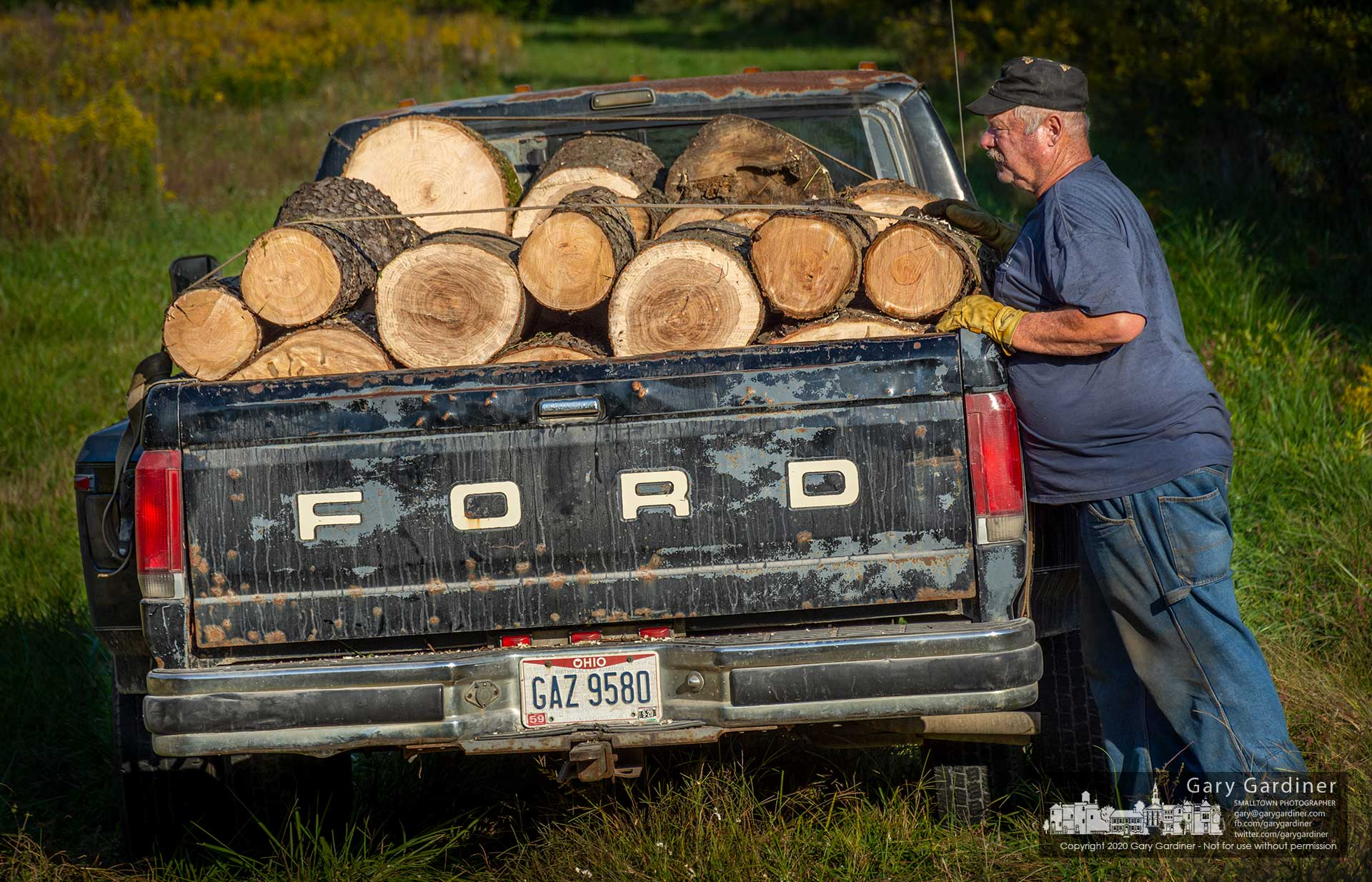 Kevin Scott checks a load of seasoned firewood loaded onto a pickup truck. My Final Photo for Sept. 25, 2020.