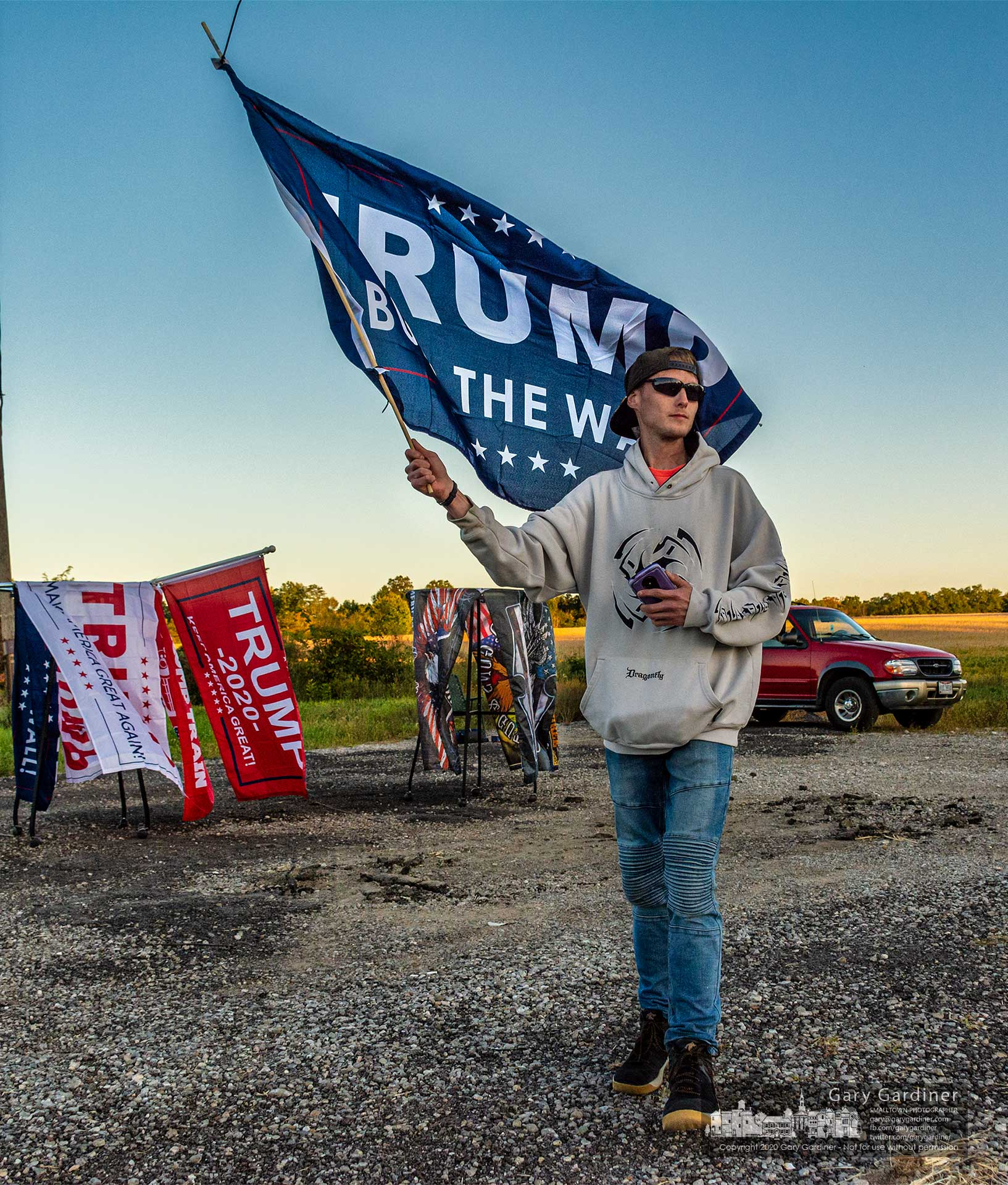 A man carries a pro-Trump sign across the graded parking lot near Marengo where he is selling flags and banners supporting Trump in his re-election campaign. My Final Photo for Sept. 20, 2020.