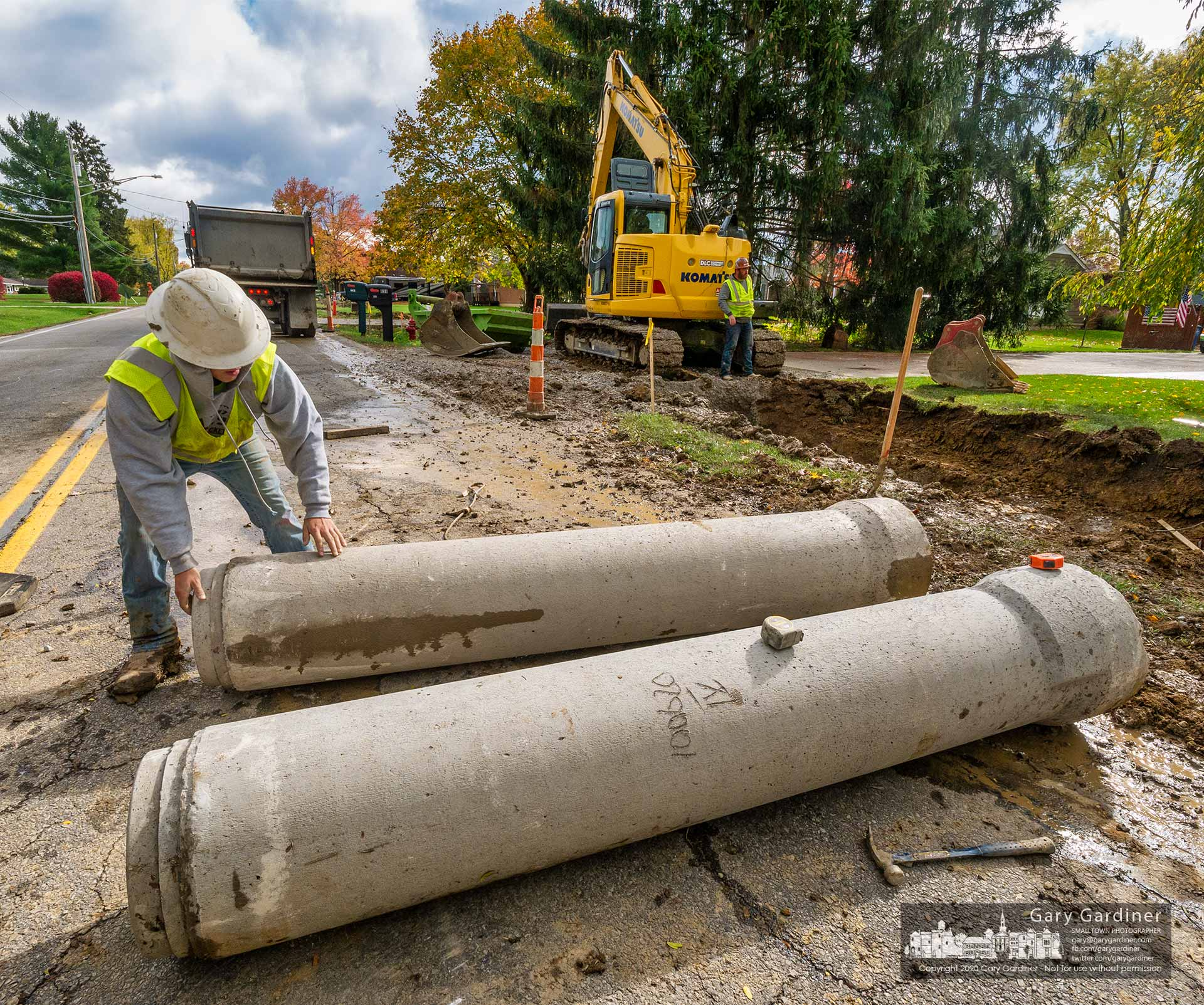 A construction worker prepares a section of storm drain for placement beneath what will be the new sidewalks on East College Ave. My Final Photo for Oct. 30, 2020.