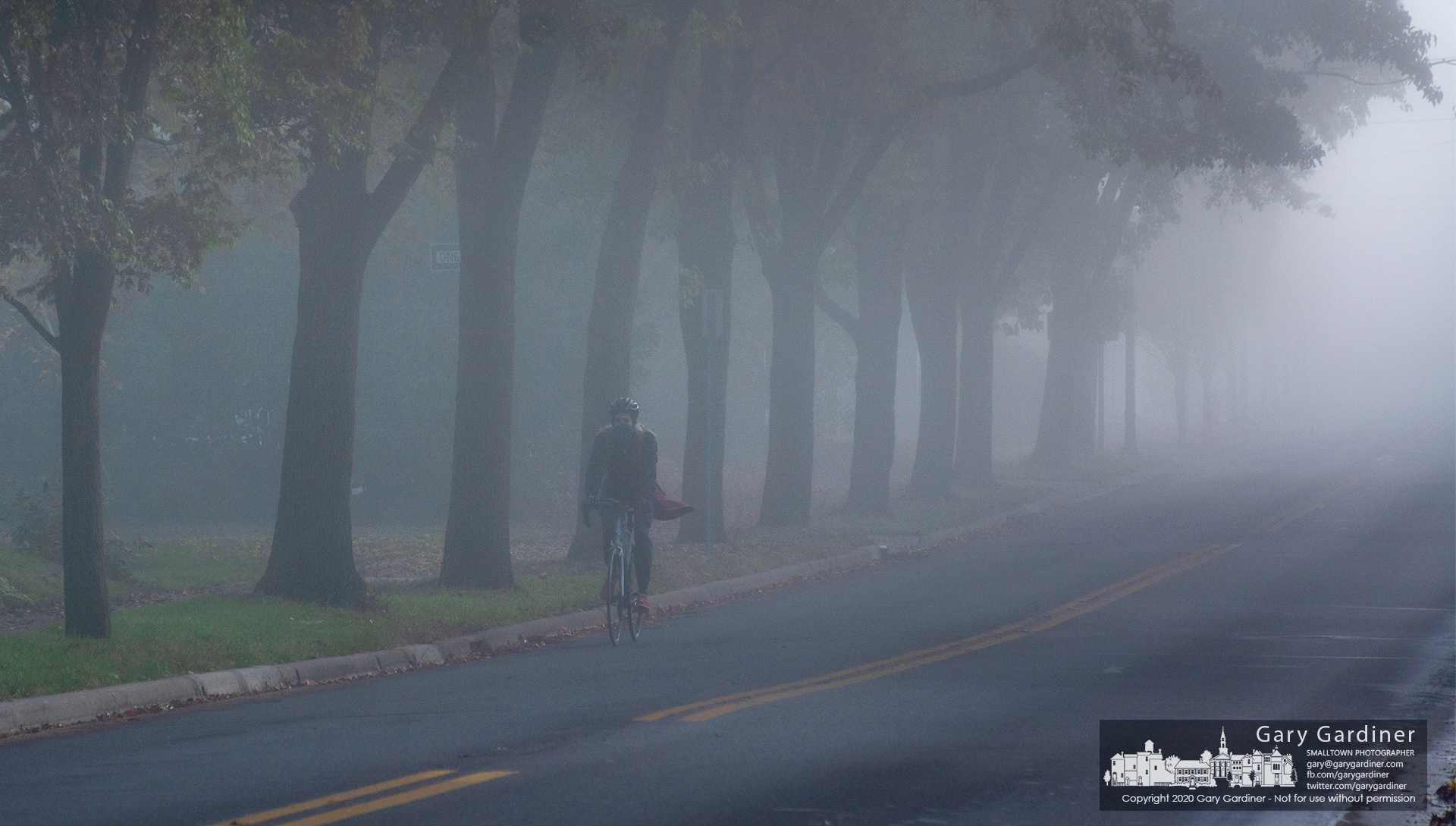 A lone bicyclist pedals westward on Main Street in the early morning fog in Westerville. My Final Photo for Oct. 22, 2020.