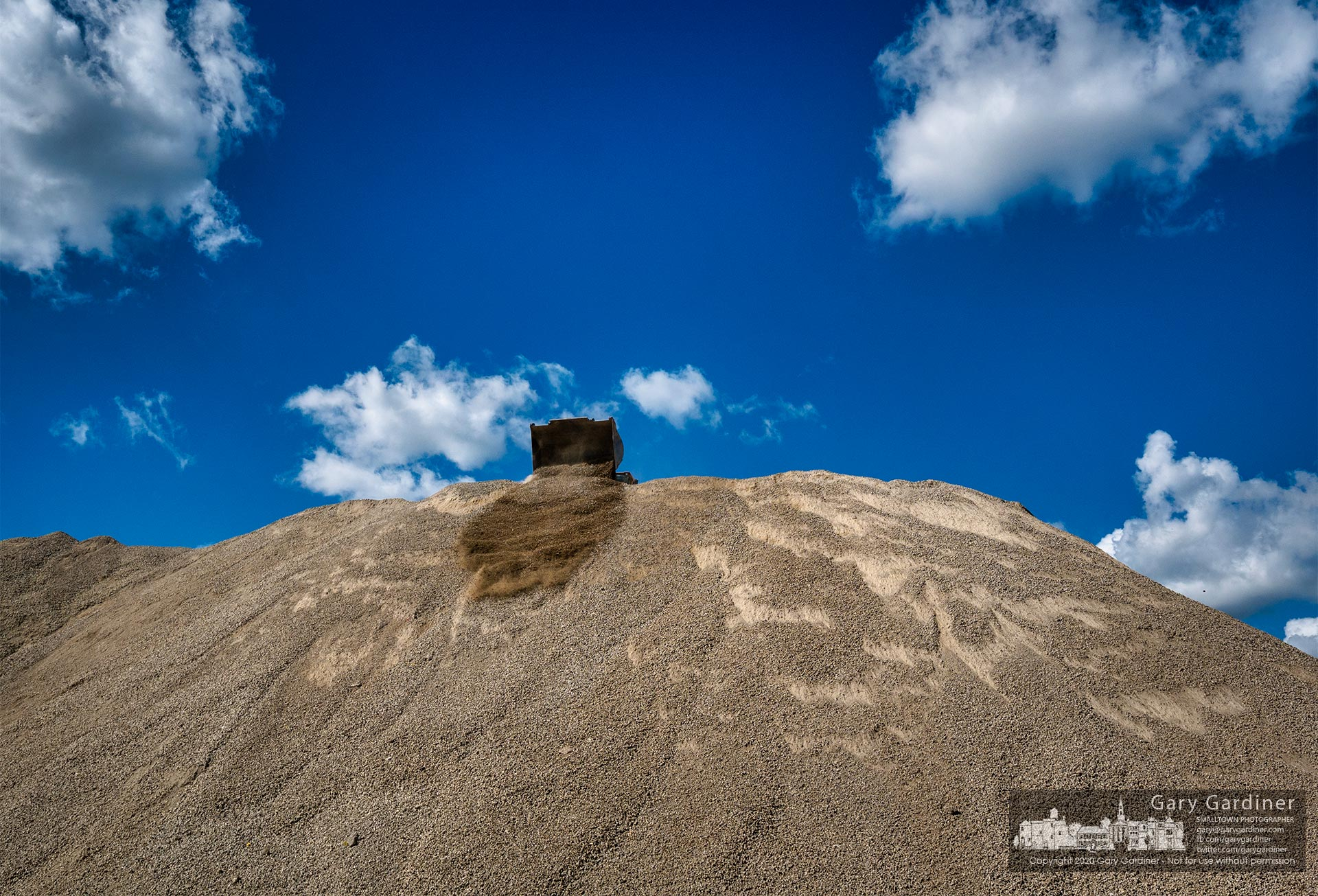 A front end loader drops recycled concrete gravel over the edge of a large mound of gravel stored for sale in a recycling yard near I270 and Westerville Road. My Final Photo for Oct. 1, 2020.