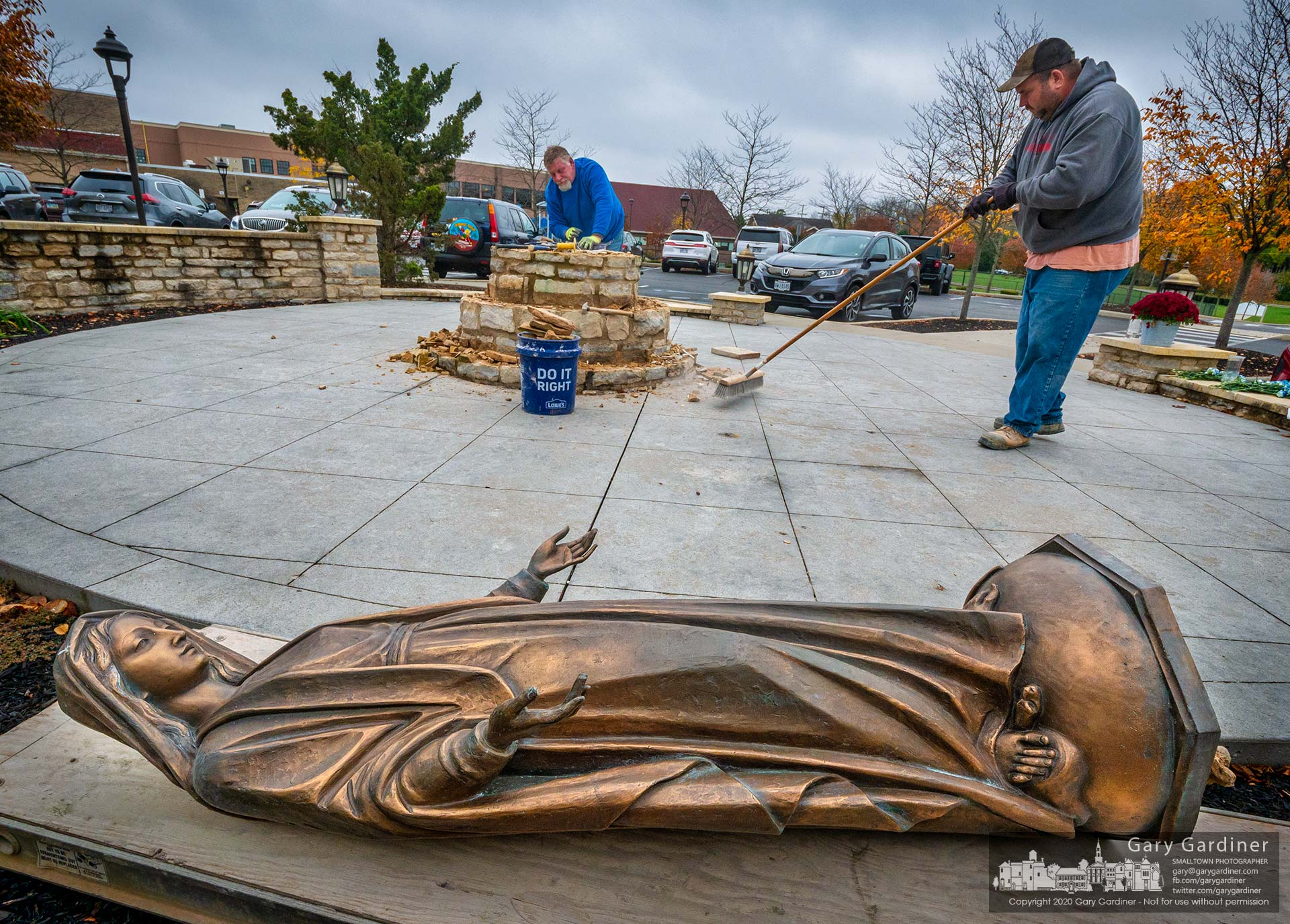 Workers repair the pedestal for the St. Paul the Apostle Catholic Church statue of Mary as it lies on its back ad the edge of a shrine at the Westerville church. My Final Photo for Oct. 27, 2020.
