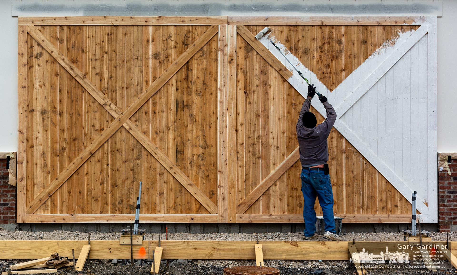 A white coat of paint gets rolled onto the faux barn door on the side of the new carwash being built in the parking lot of West Park Plaza on Huber Village BNlvd. My Final Photo for Nov. 20, 2020.