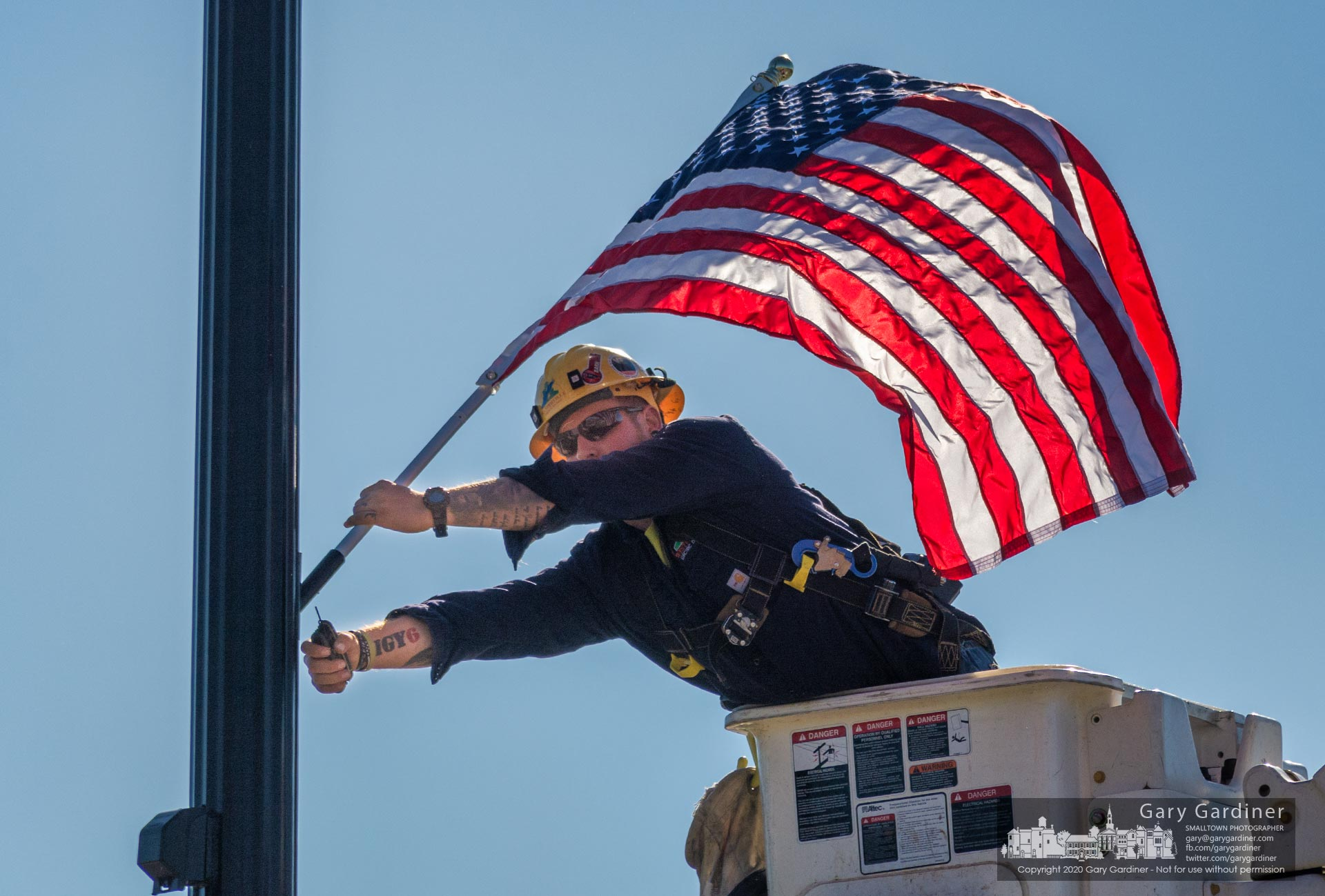 A city worker attaches an American flag to a utility pole on South State in anticipation of Veterans Day Nov. 11, 2020. My Final Photo for Nov. 4, 2020.