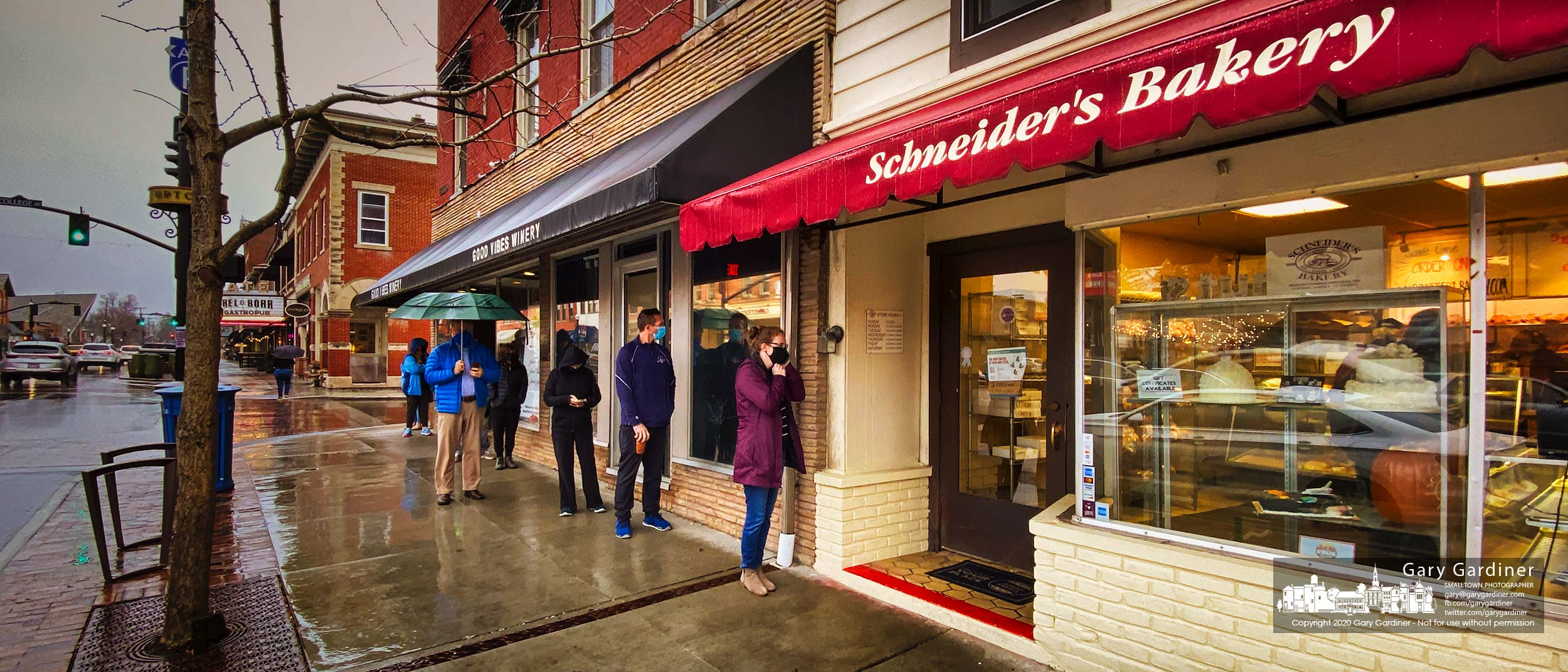 Customers line up at the proper social distance to step into Schneider's Bakery to pick up their Thanksgiving rolls, breads, pies, cakes, cookies, and donuts. My Final Photo for Nov. 25, 2020.