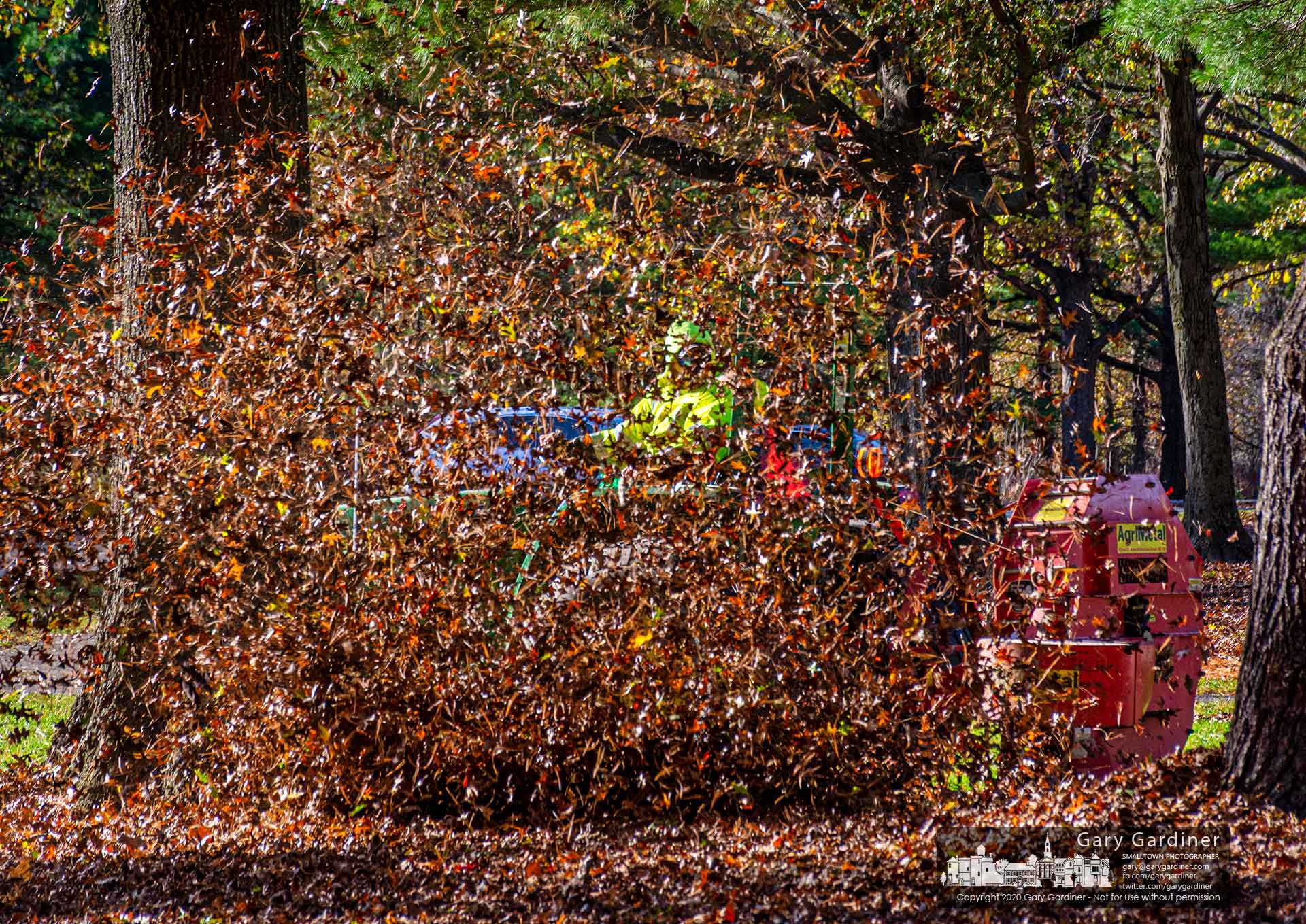A worker driving a tractor pulling an industrial blower is obscured by leaves being cleared from the grounds at Sharon Woods Metro Park. My Final Photo for Nov. 2, 2020.