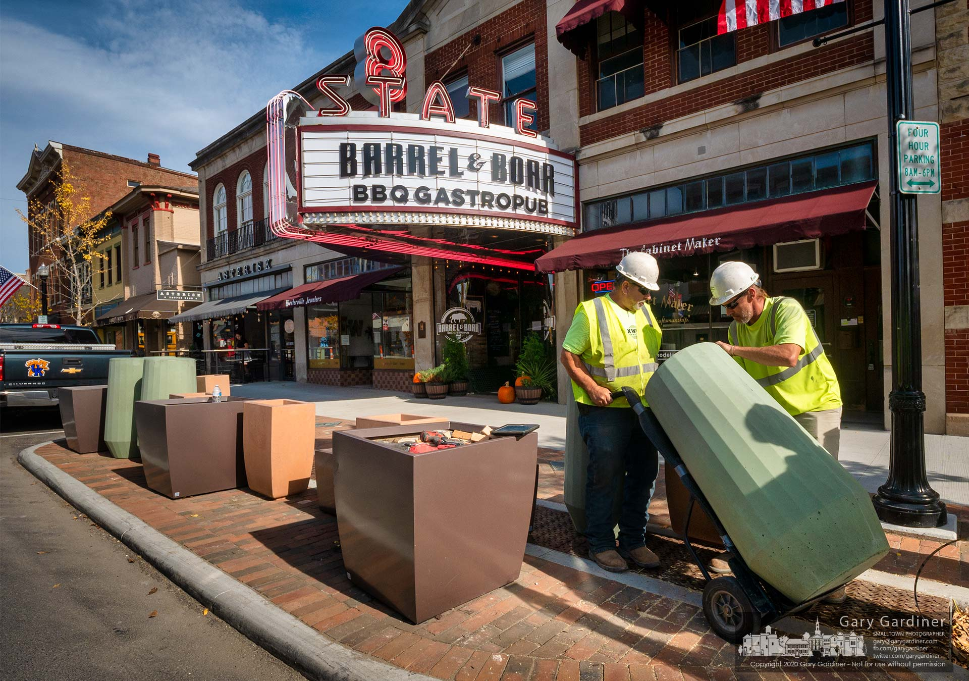 Workers place a variety of shaped and sized planters onto the bumpout in front of Barrel & Boar Restaurant to act as bollards to prevent vehicles from running into the marquee. My Final Photo for Nov. 5, 2020.