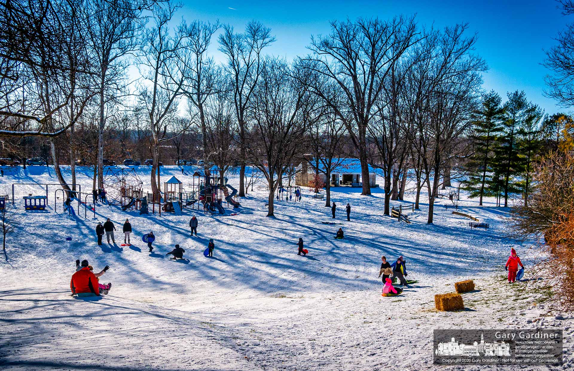 A collection of children, their parents, and friends take advantage of the fresh coating of snow laid over melted and frozen snow from an earlier fall to enjoy a day of rapidly descending the small sledding hill at Alum Creek Park in Westerville. My Final Photo for Dec. 26, 2020.