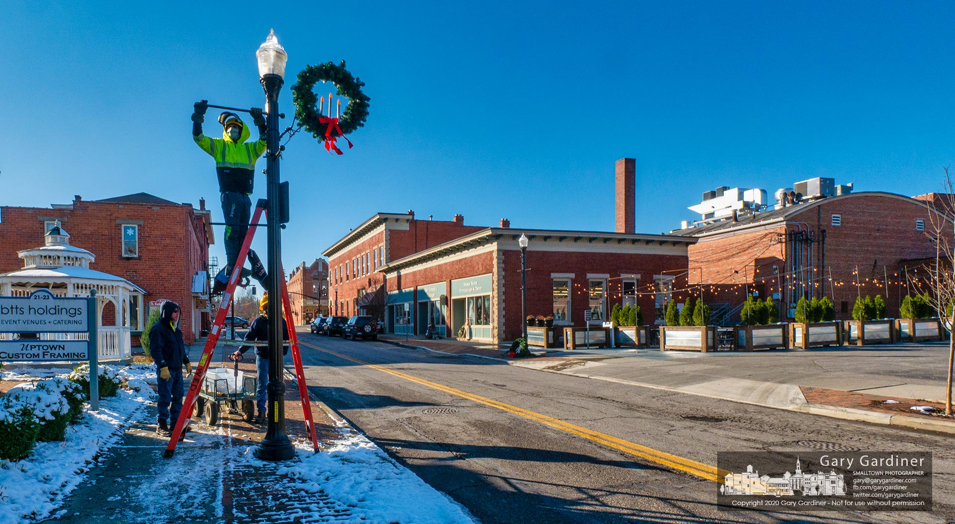 City workers install Christmas season banners on the light poles in Uptown Westerville with plans later in the week to raise the Christmas Star at State and Main. My Final Photo for Dec. 2, 2020.