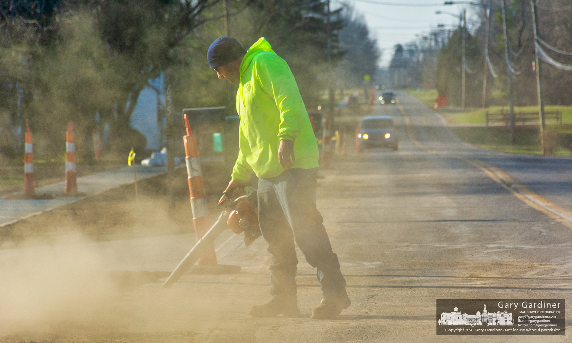 A construction worker blows dust and debris from East College Ave. as the crew finished the day laying topsoil along the edges of the new sidewalk recently finished on the east-west corridor road. My Final Photo for Dec. 9, 2020.
