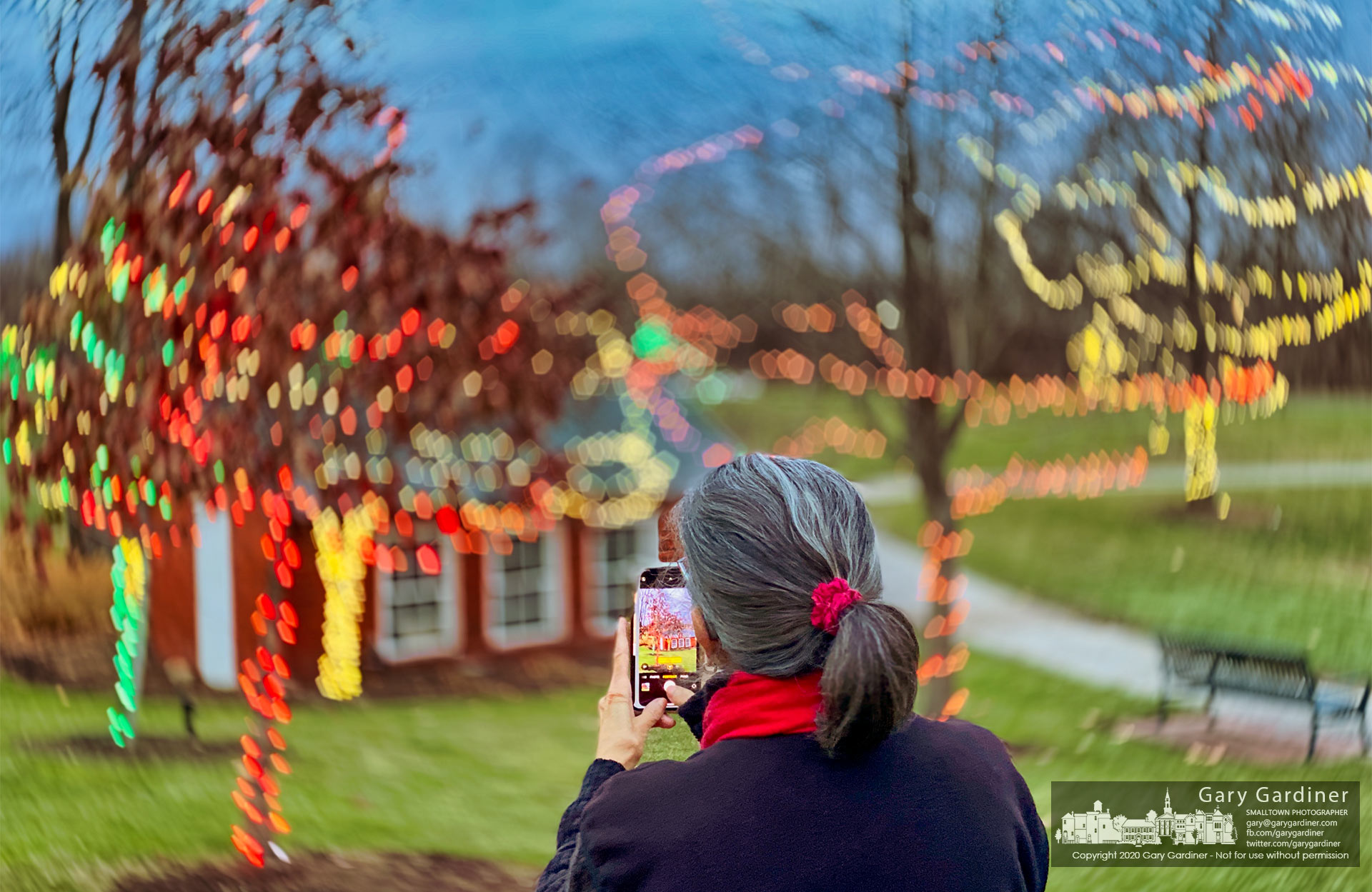 A woman pauses to photograph trees festooned with colored lights as part of the Christmas season decorations at Heritage Park in Westerville. My Final Photo for Dec. 8, 2020.