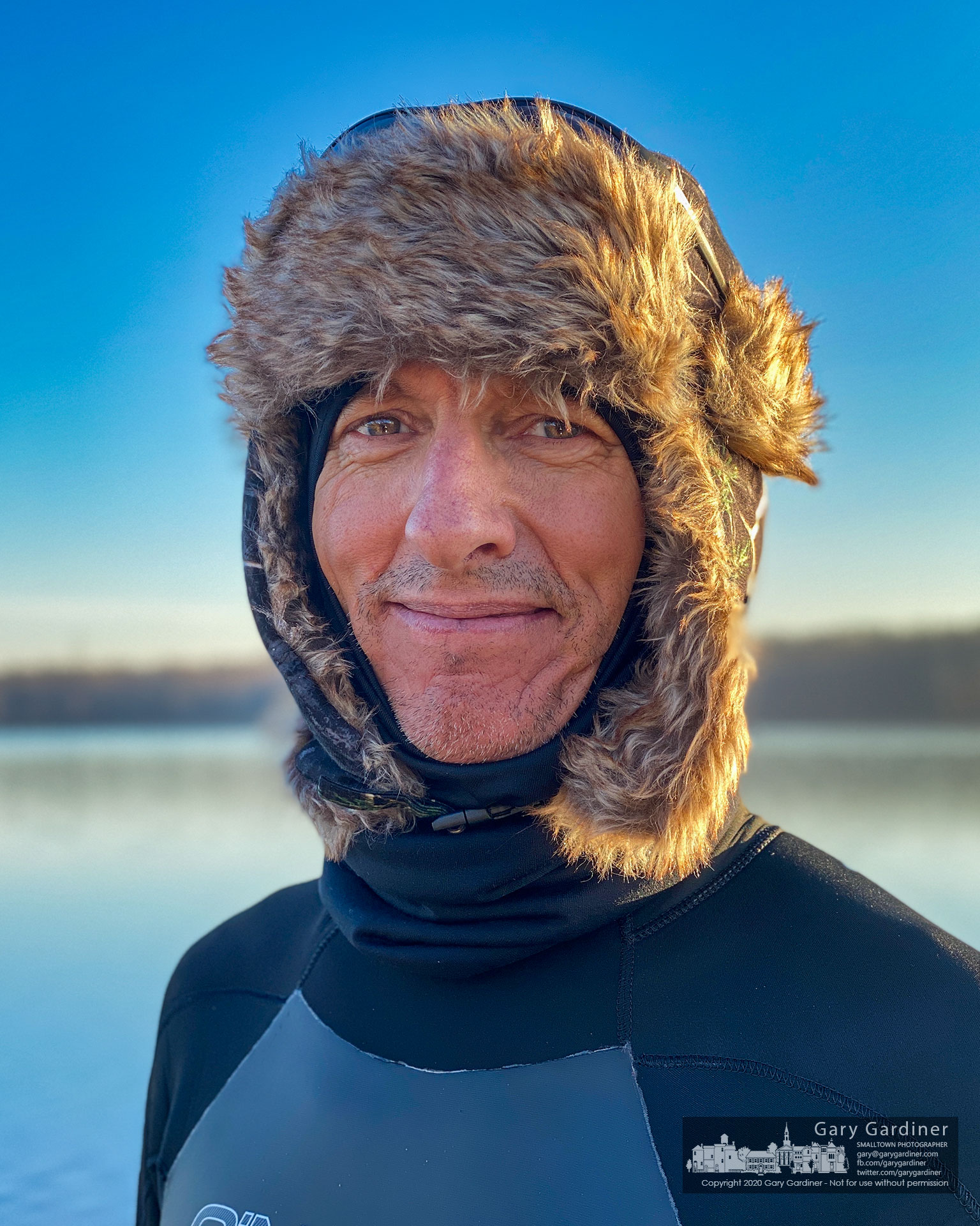 Endurance athlete Don Cain, wearing a wetsuit and a winter head-covering, poses for a photo after completing his morning workout aboard a paddleboard on the icy waters of Hoover Reservoir. My Final Photo for Dec. 29, 2020.