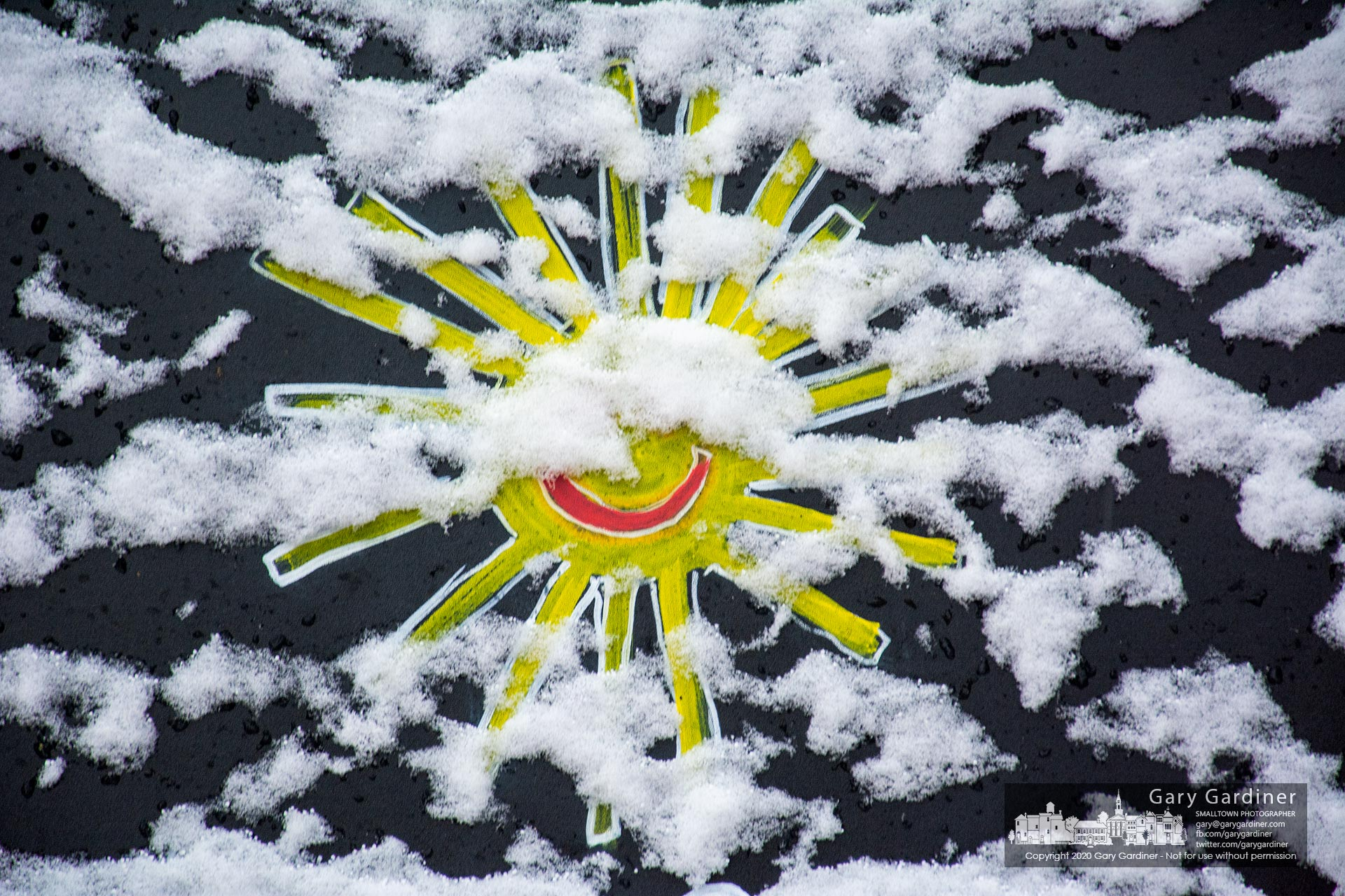 A scattering of snow covers a smiling sun painted on the sandwich board advertising Totadalicious on South State Street after an overnight storm. My Final Photo for Dec. 1, 2020.