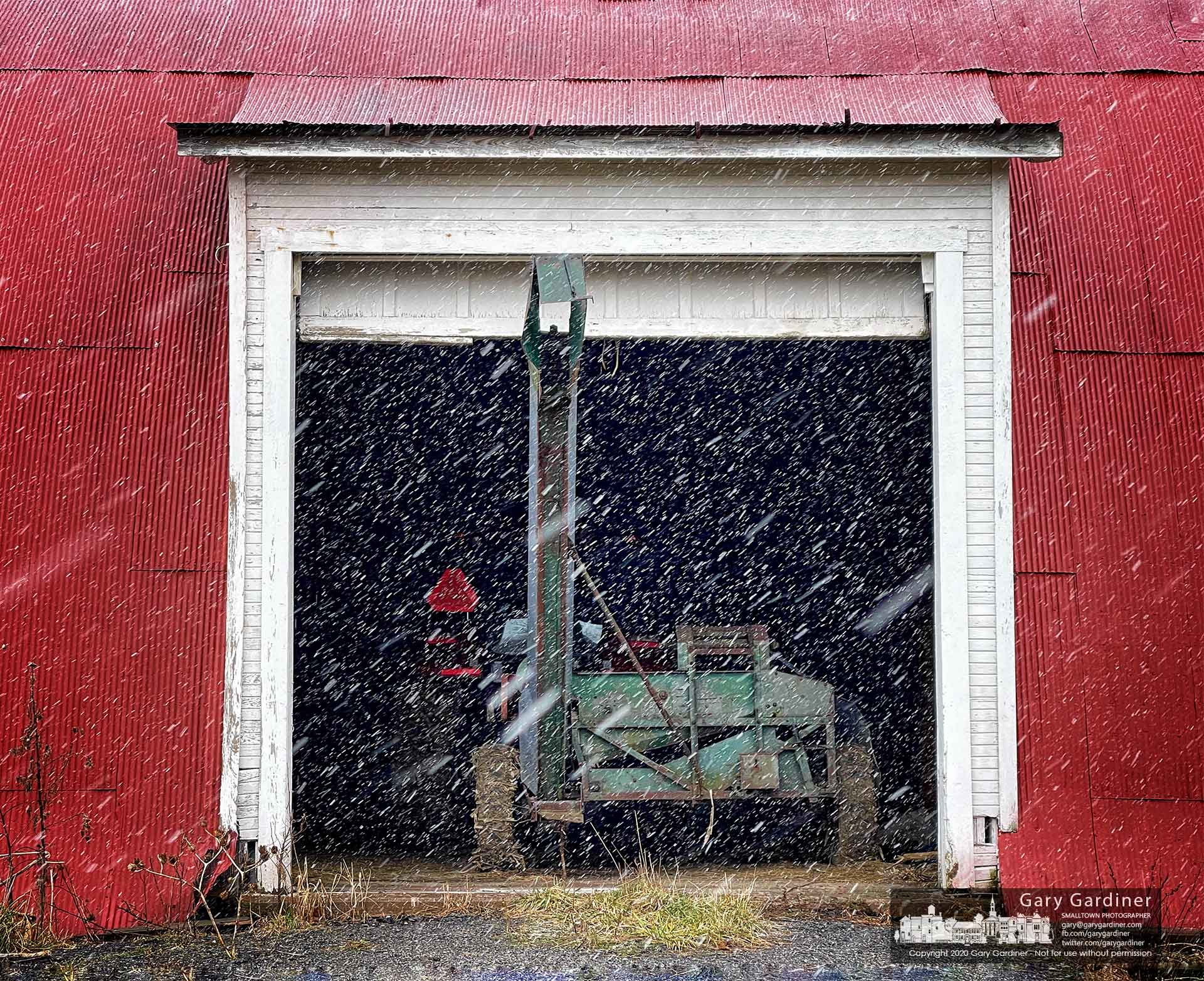 A heavy snow squall blows across the open door of the barn at the Braun Farm where a corn picker waits for repairs. My Final Photo for Jan. 17, 2021.